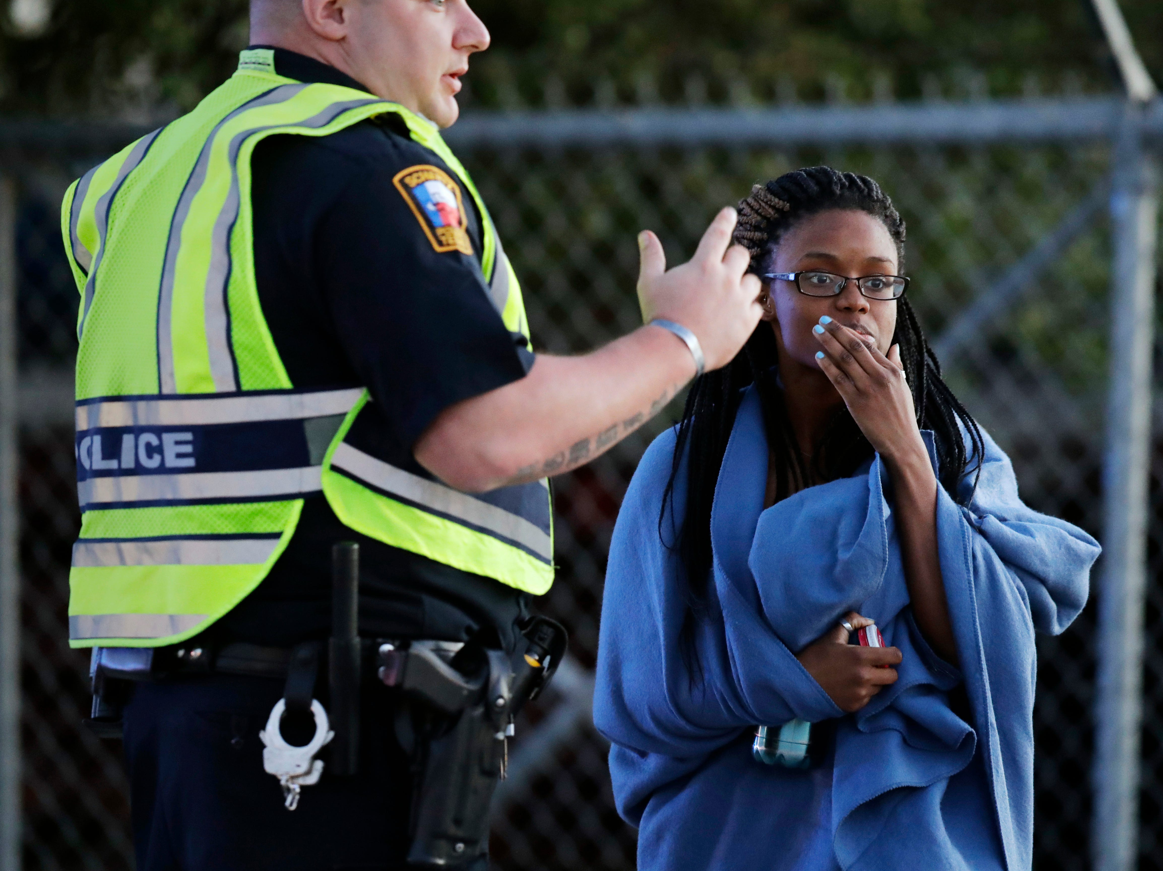 March 20, 2018: An employee wrapped in a blanket talks to a police officer after she was evacuated at a FedEx distribution center where a package exploded in Schertz, Texas. Authorities believe the package bomb is linked to the recent string of Austin bombings.