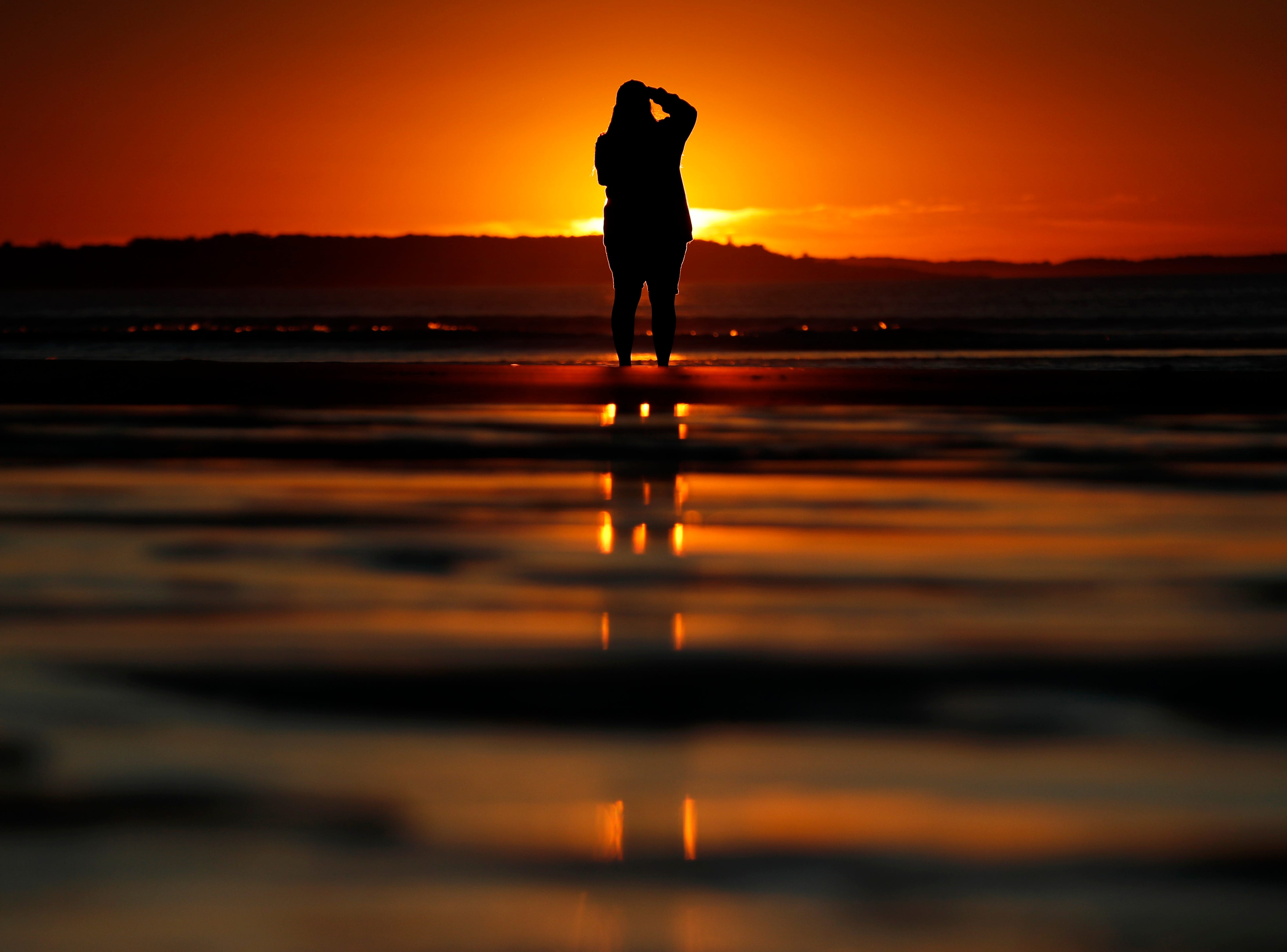 July 12, 2018: Consuello Jessop, of Providence, R.I., photographs the sunrise at Ocean Park in Old Orchard Beach, Maine.