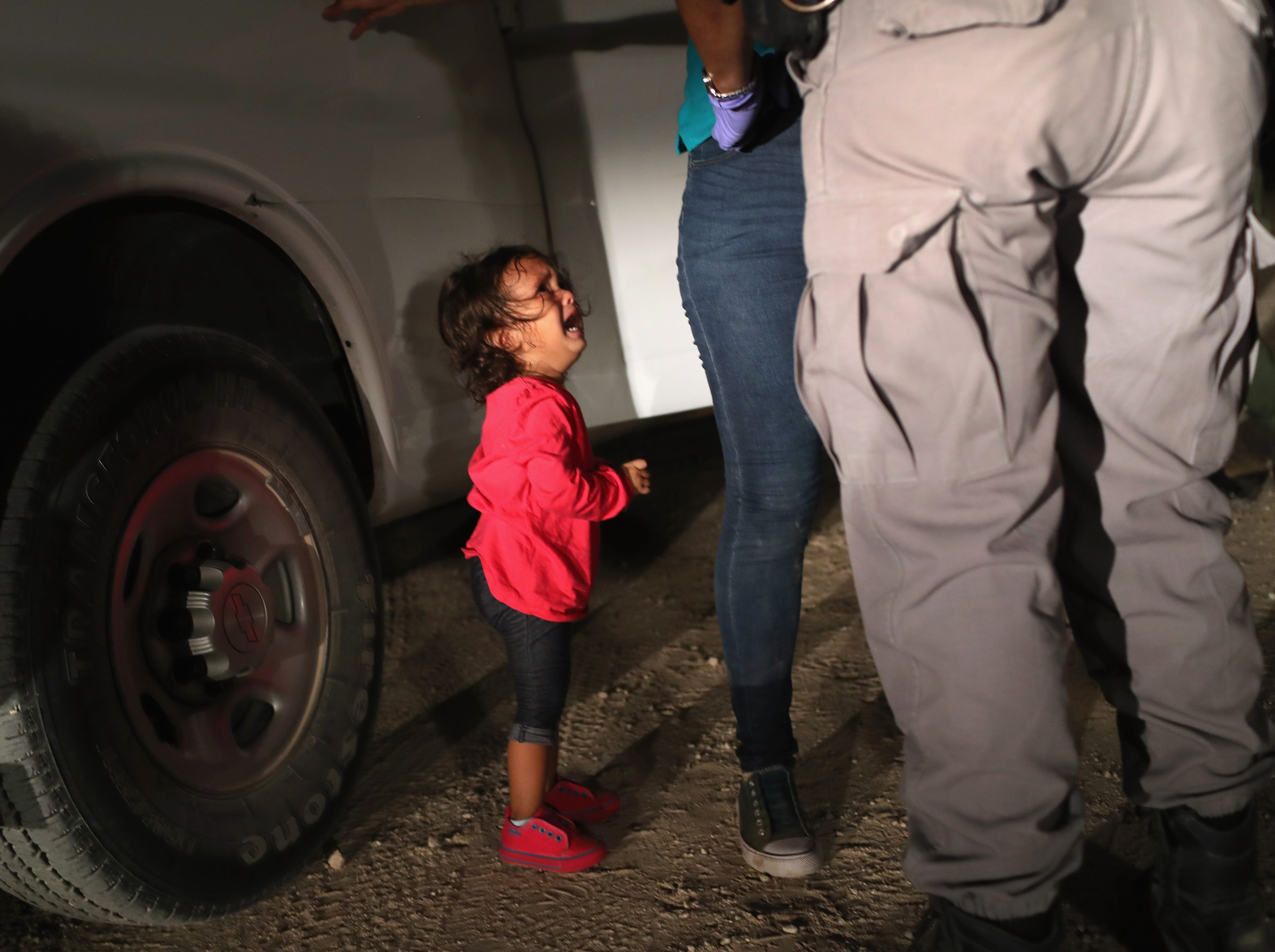 """June 12, 2018: A two-year-old Honduran asylum seeker cries as her mother is searched and detained near the U.S.-Mexico border in McAllen, Texas. The asylum seekers had rafted across the Rio Grande from Mexico and were detained by U.S. Border Patrol agents before being sent to a processing center for possible separation. Customs and Border Protection (CBP) is executing the Trump administration's """"zero tolerance"""" policy towards undocumented immigrants."""
