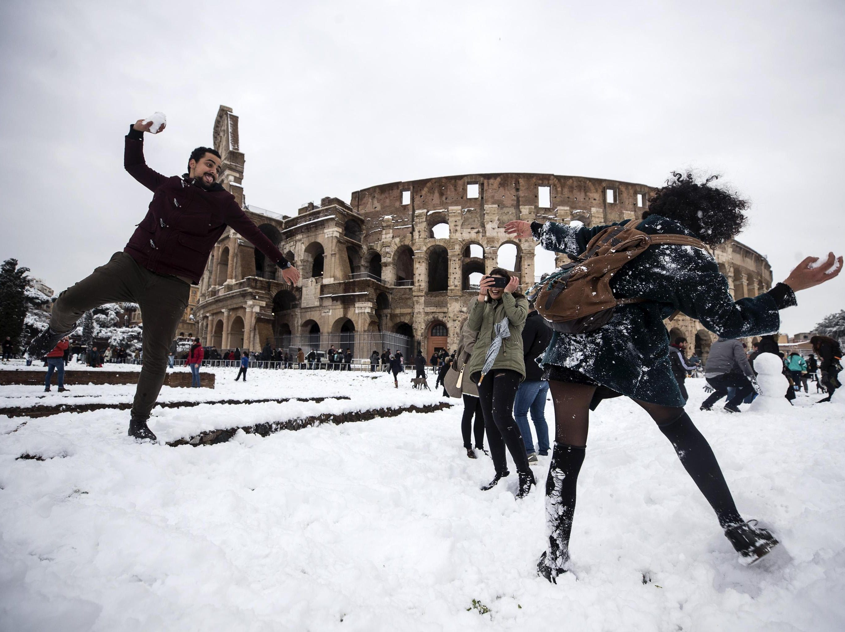 Feb. 26, 2018: People take part in a snowball fight in front of the Colosseum covered by snow during a snowfall in Rome, Italy.