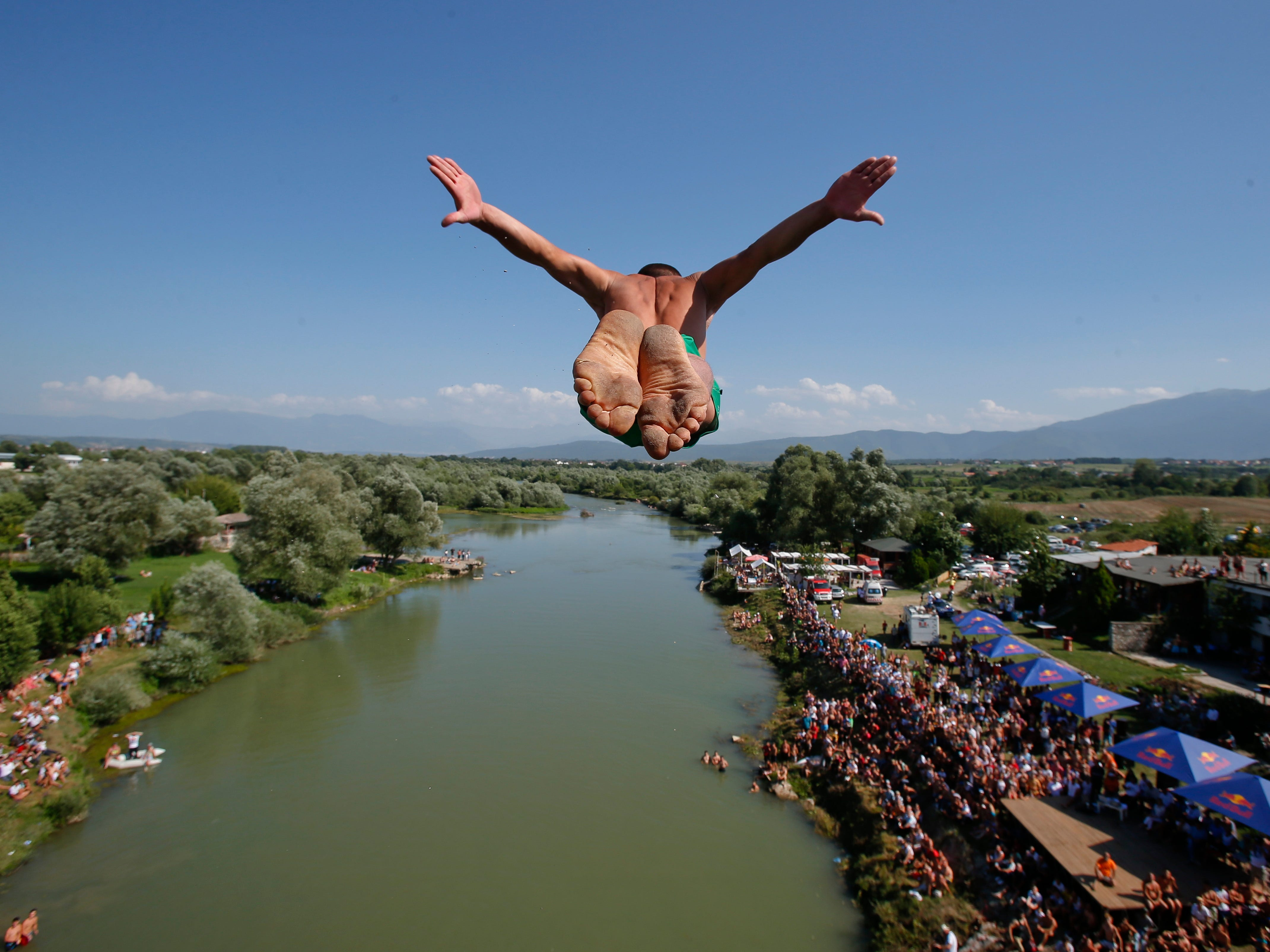 July 22, 2018: Spectators watch from the river banks as a diver launches from the Ura e Shejnt bridge during the 68th traditional annual high diving competition, near the town of Gjakova, Kosovo.