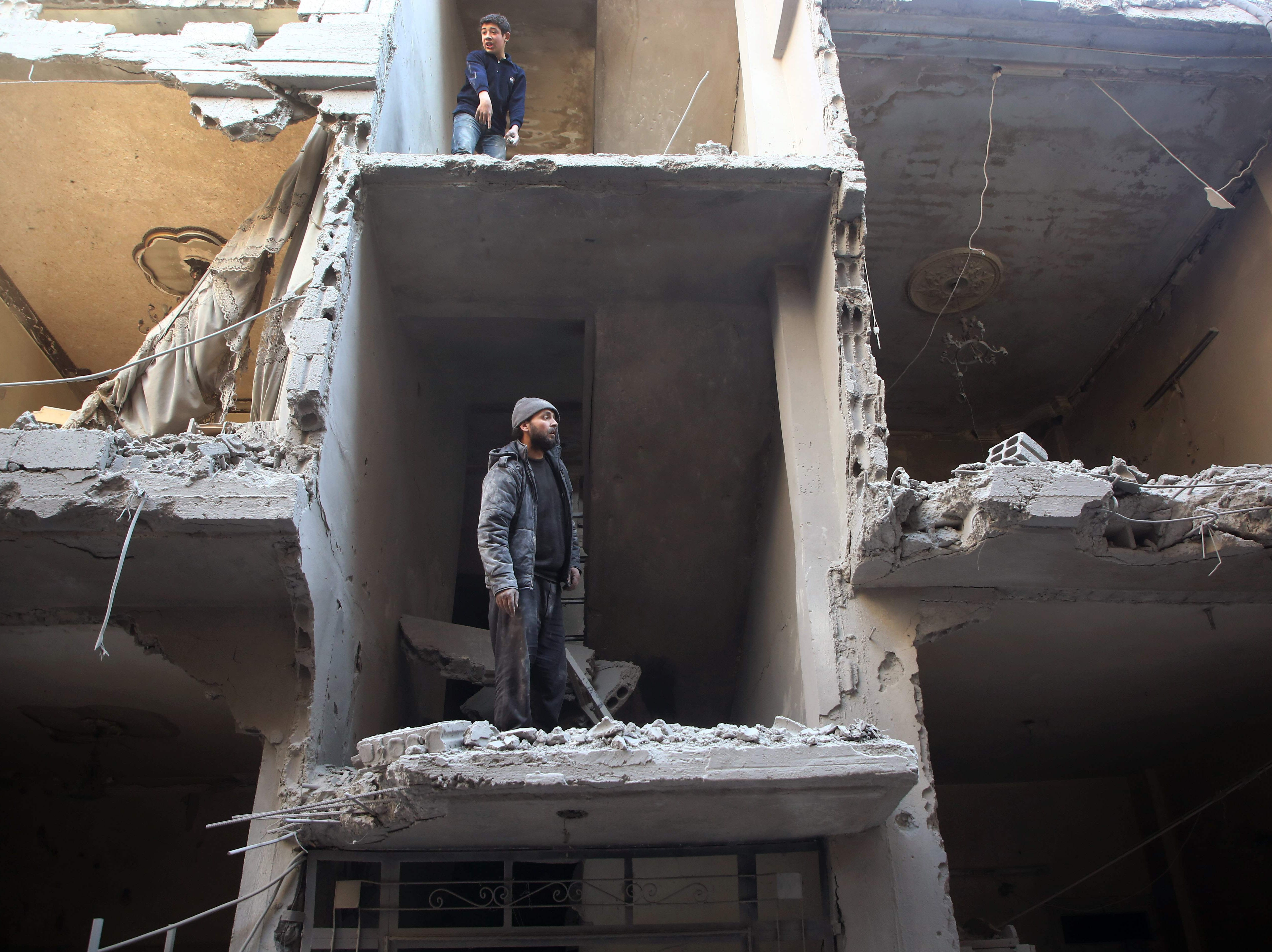 Feb. 1, 2018: Syrians inspect the damage in a residential building hit in air strikes by regime forces on Arbin, in the rebel-held Eastern Ghouta region.