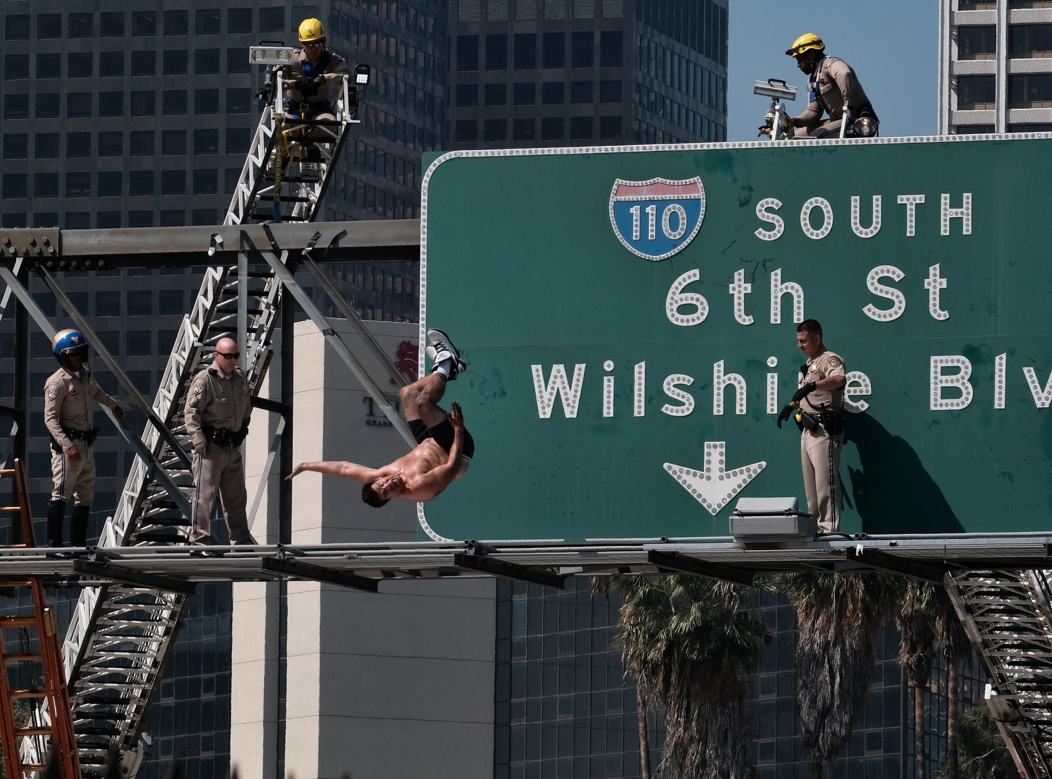 June 27, 2018: California Highway Patrol officers watch as a man jumps from a highway sign in downtown Los Angeles. The man suspended banners, one about fighting pollution, after climbing onto the sign over State Route 110 during the morning rush hour. The man did a backflip from the sign and landed on a huge inflated airbag deployed in traffic lanes by firefighters.