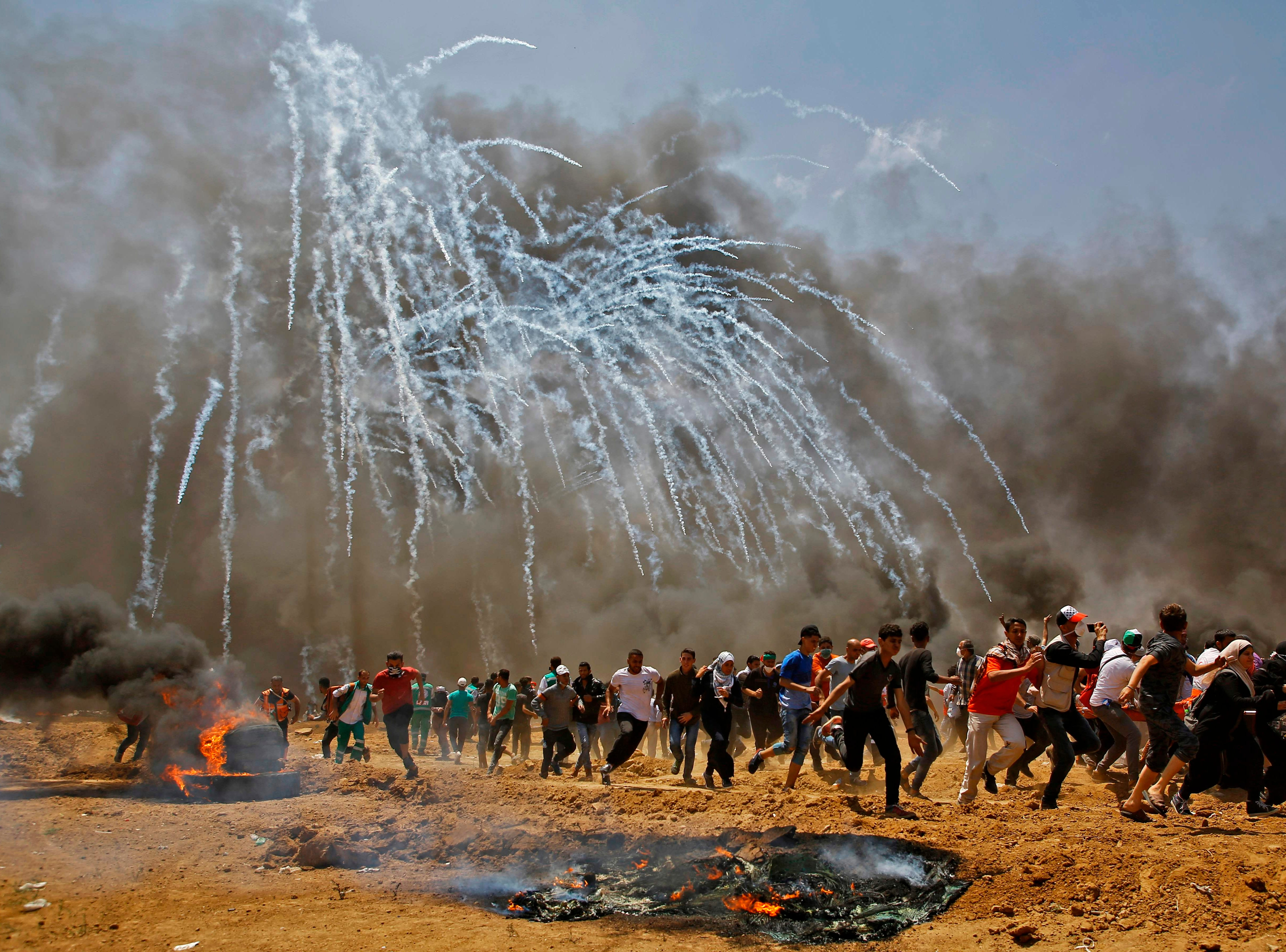 May 14, 2018: Palestinians run for cover from tear gas during clashes with Israeli security forces near the border between Israel and the Gaza Strip, east of Jabalia as Palestinians protest over the inauguration of the US embassy following its controversial move to Jerusalem.