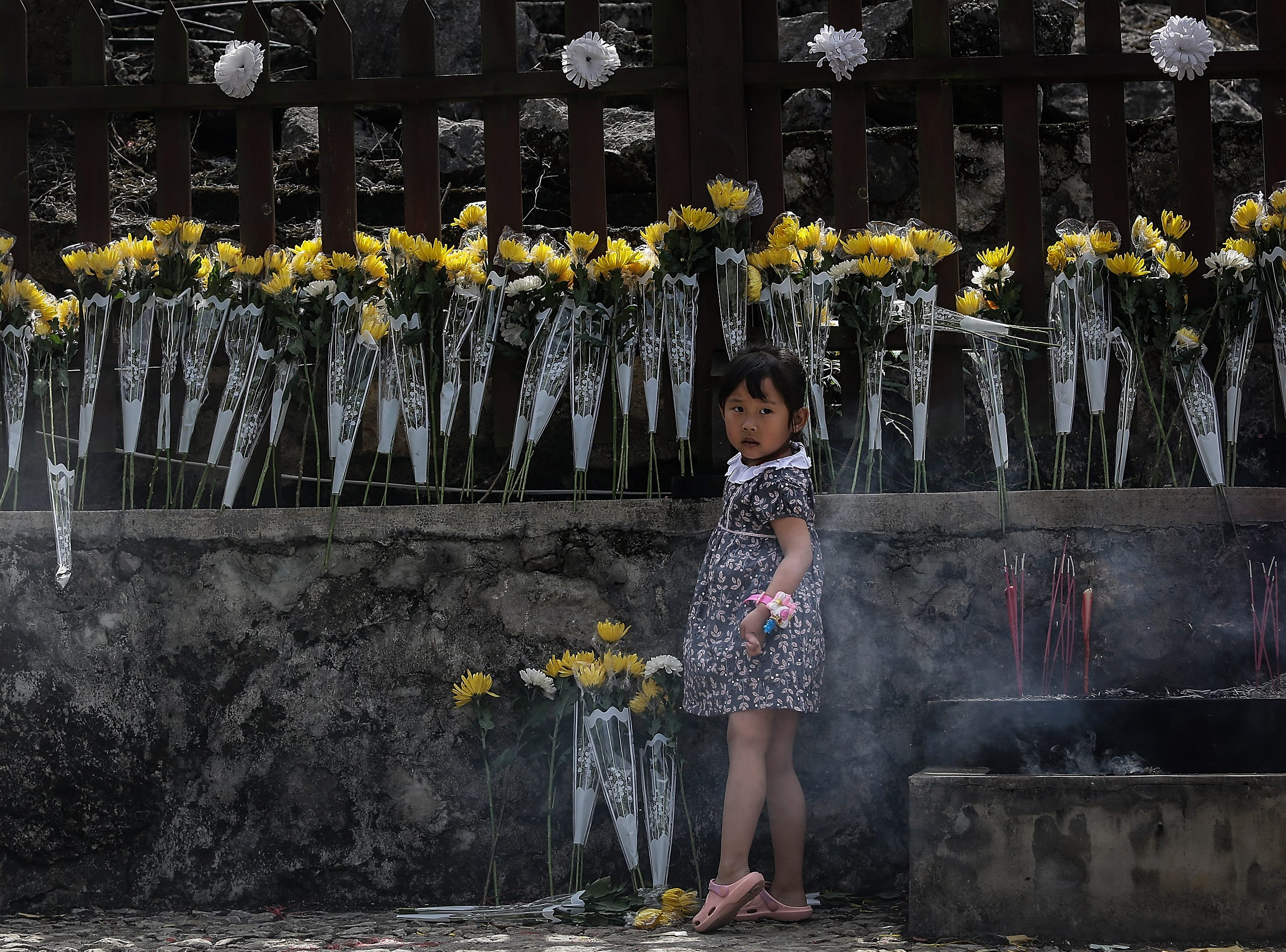 May 12, 2018: A girl lays flowers to mourn for the victims at the ruins of earthquake-hit Beichuan county during the ten-year anniversary in the Sichuan province of China. The Beichuan county was relocated a decade after it was destroyed by the May 12, 2008 earthquake in which more than 15,000 people died.