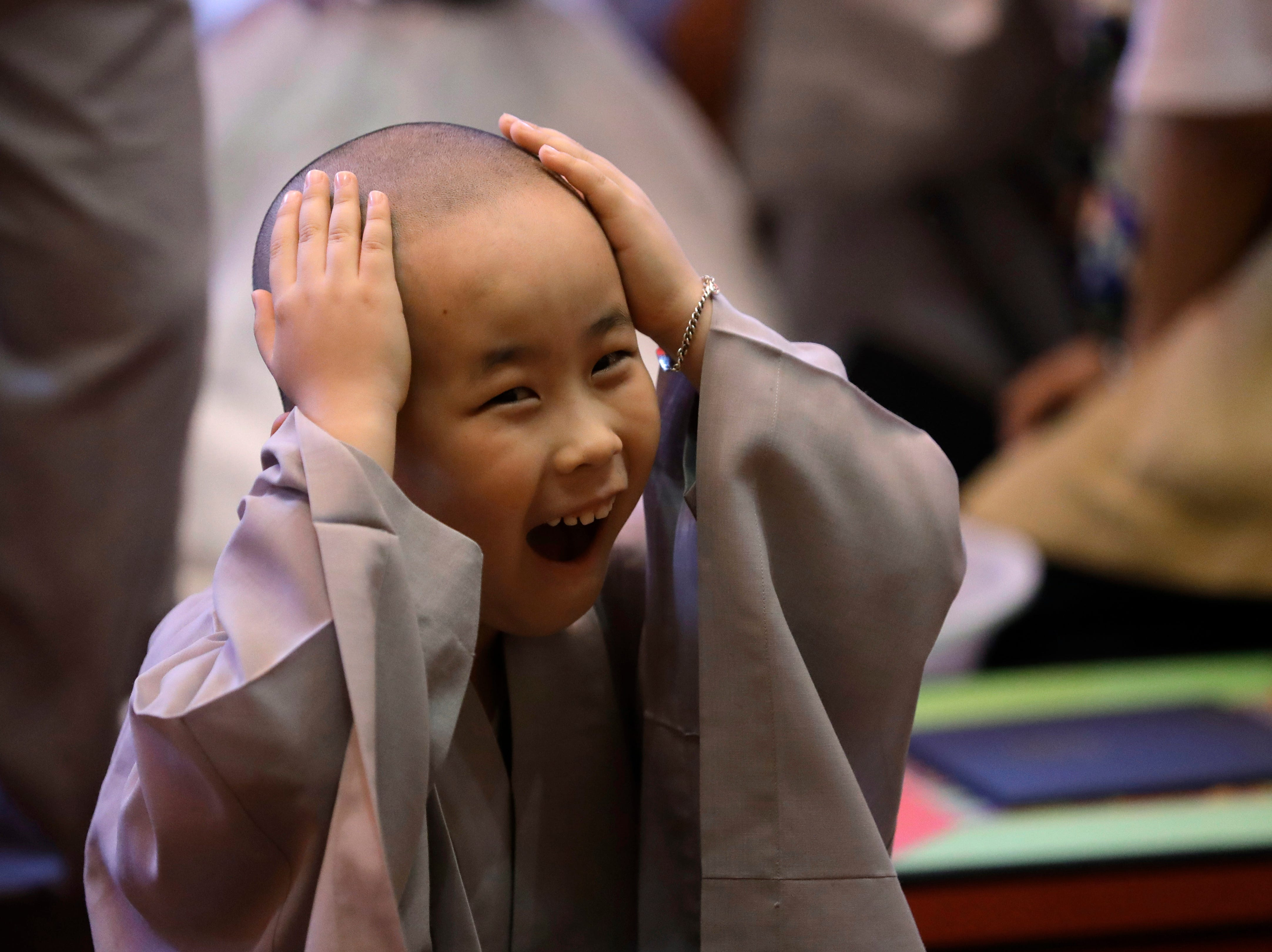 May 2, 2018: A boy, whose Buddhist name is Da Sun, touches his newly shaved head during a service to have an experience of the lives of Buddhist monks, at the Jogye Temple in Seoul, South Korea.