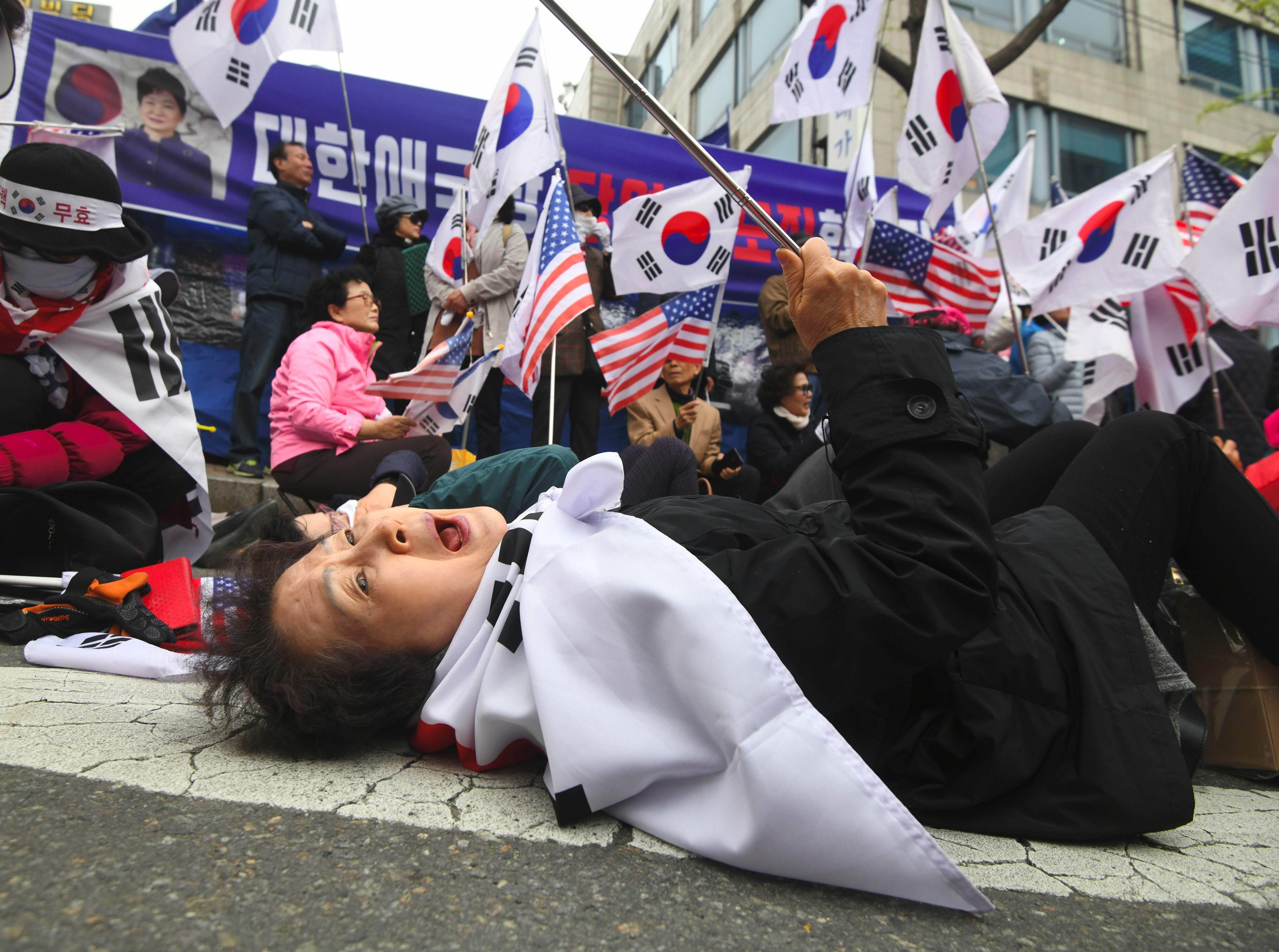 April 6, 2018: A supporter of South Korea's former President Park Geun-hye reacts after a court sentenced Park Geun-hye to 24 years in prison, during a rally outside the Seoul Central District Court in Seoul. South Korea's disgraced former president Park Geun-hye was jailed for 24 years on April 6, for corruption, closing out a dramatic fall from grace for the country's first woman leader who became a figure of public fury and ridicule.
