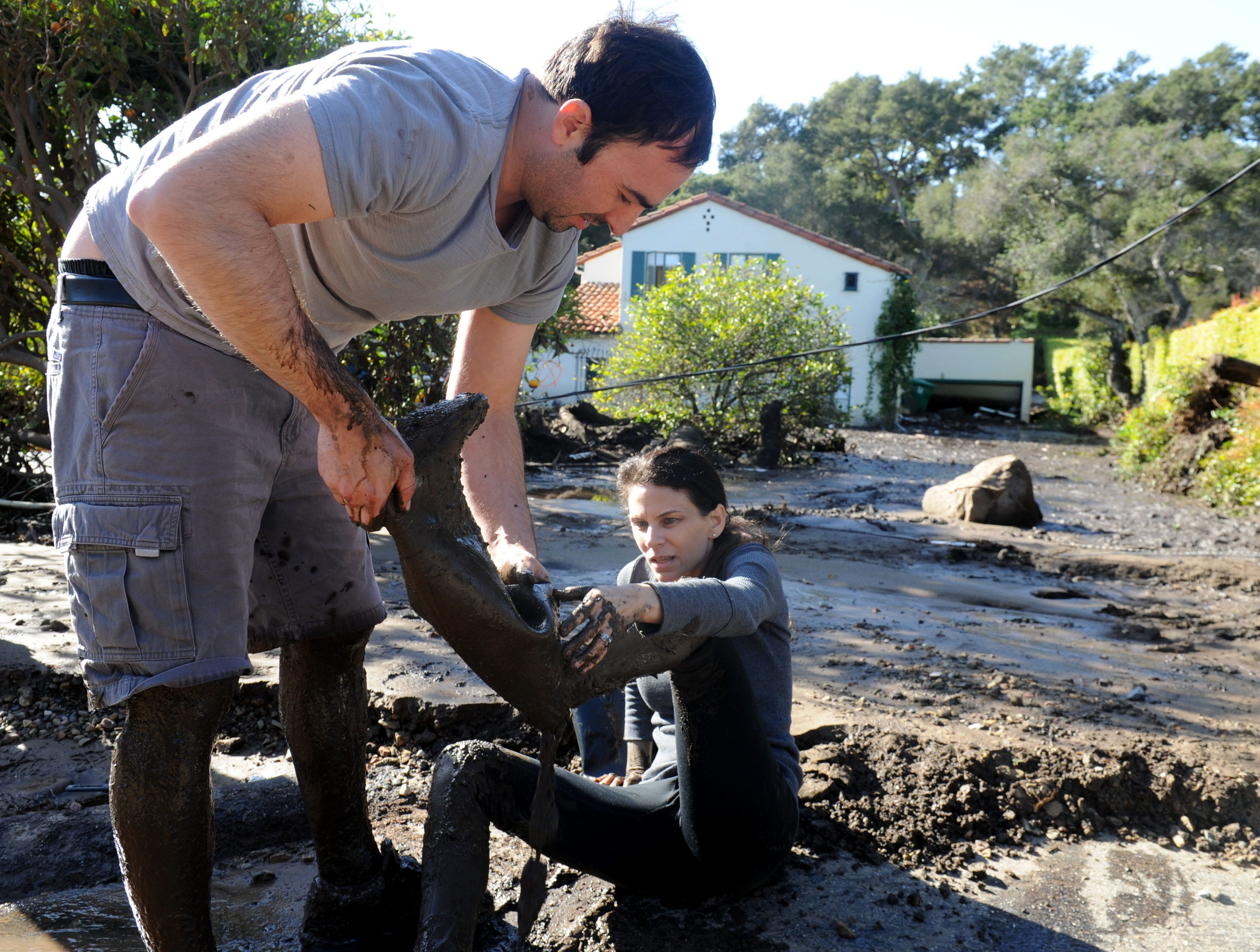 Jan. 10, 2018: A couple of residents take their boots off after attempting to walk on two feet of mud to get to their flooded house in Montecito, Calif.