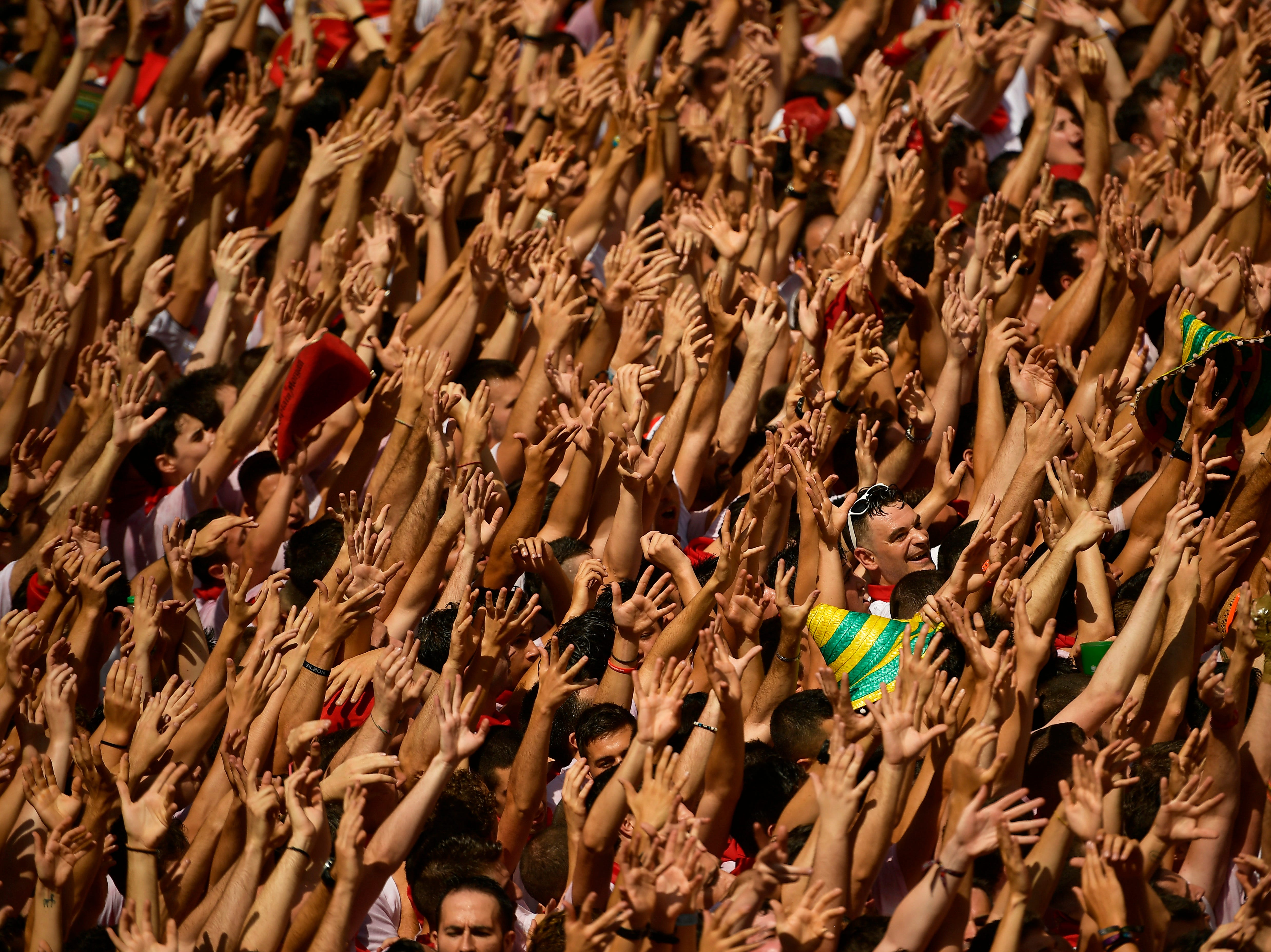July 6, 2018: Revellers hold their arms up during the launch of the 'Chupinazo' rocket, to celebrate the official opening of the 2018 San Fermin fiestas with daily bull runs, bullfights, music and dancing in Pamplona, Spain.