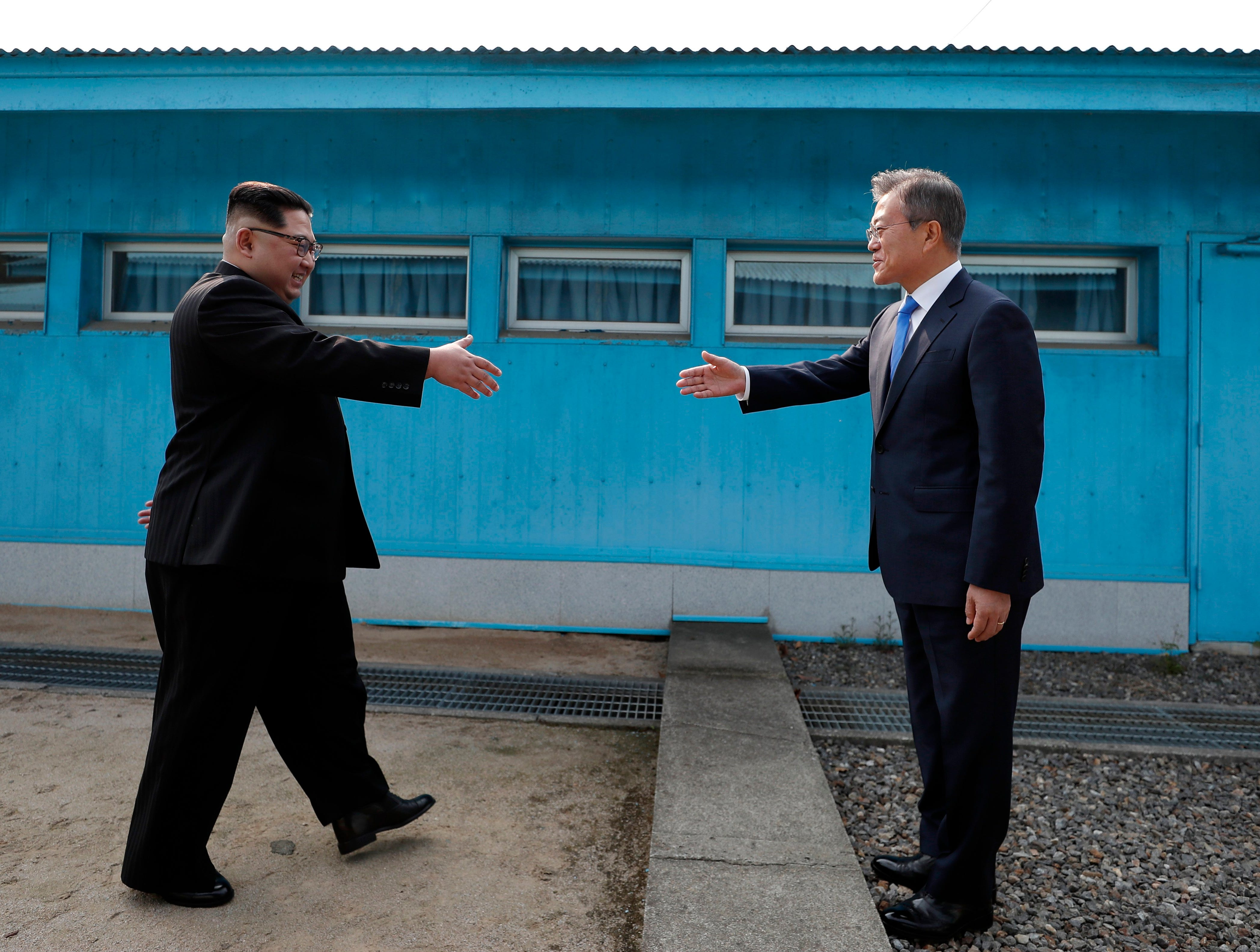 April 27, 2018: North Korean leader Kim Jong-un (L) shakes hands with South Korean President Moon Jae-in (R) between the military demarcation line (MDL), at the Joint Security Area (JSA) on the Demilitarized Zone (DMZ) in the border village of Panmunjom in Paju, South Korea. South Korean President Moon Jae-in and North Korean leader Kim Jong-un are meeting at the Peace House in Panmunjom for an inter-Korean summit. The event marks the first time a North Korean leader has crossed the border into South Korea since the end of hostilities during the Korean War.