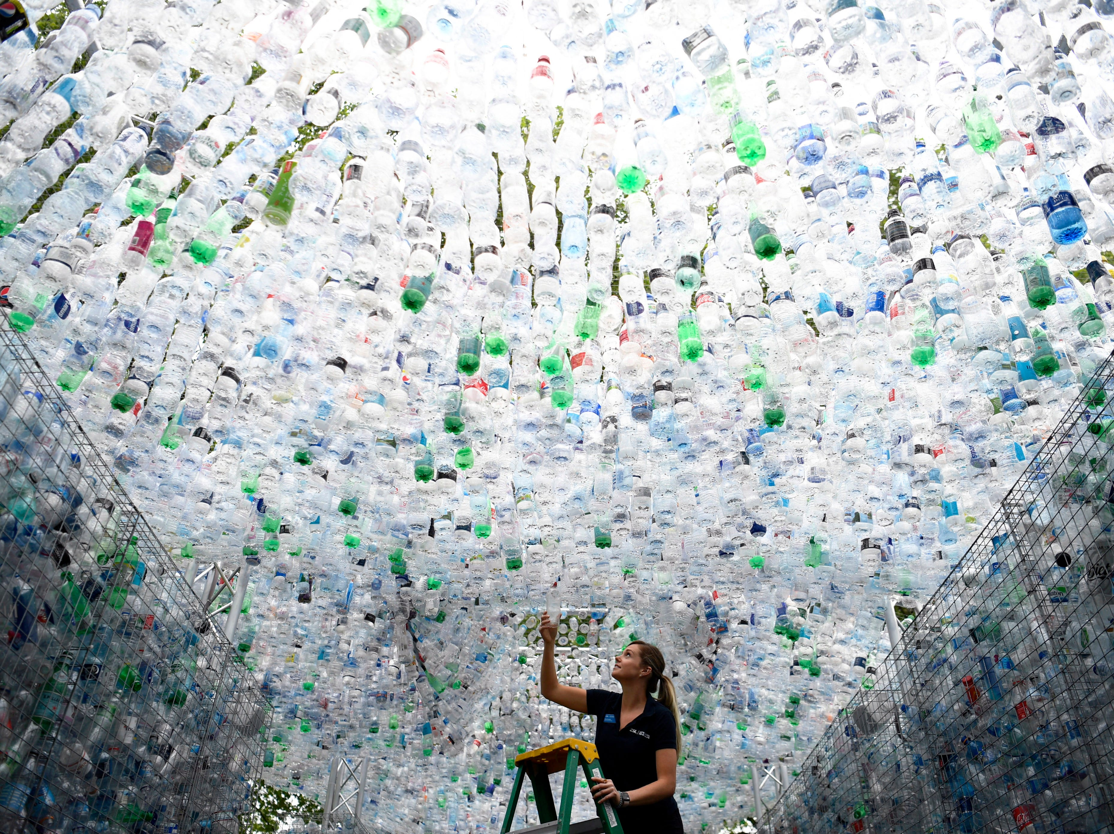 """May 24, 2018: A worker places a finishing touch on the sculpture """"Waste of Space"""" by British artist Nick Wood at the London Zoo. """"Waste of Space"""" is an installation made from 15,000 discarded single use bottles collected from London's waterways. The sculpture represents the amount of single use bottle that are purchased every minute in Britain."""