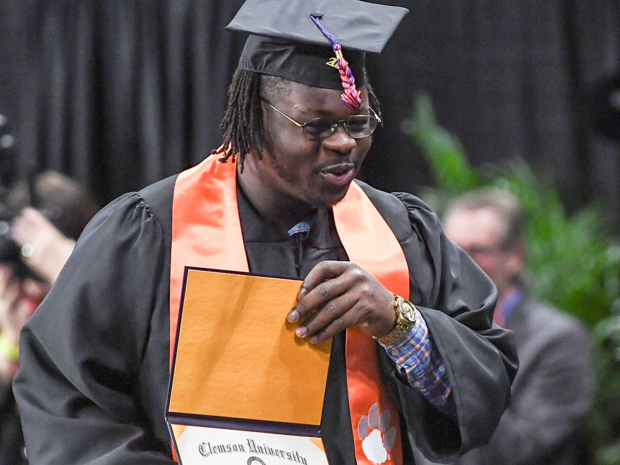 Clemson defensive lineman Albert Huggins shows his diploma during Clemson University graduation ceremony Thursday morning in Littlejohn Coliseum in Clemson.