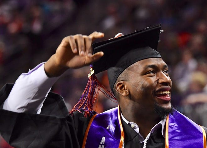 Clelin Ferrell, a Clemson football player, celebrates after getting his diploma during the graduation ceremony at Clemson University on Thursday, Dec. 20, 2018.