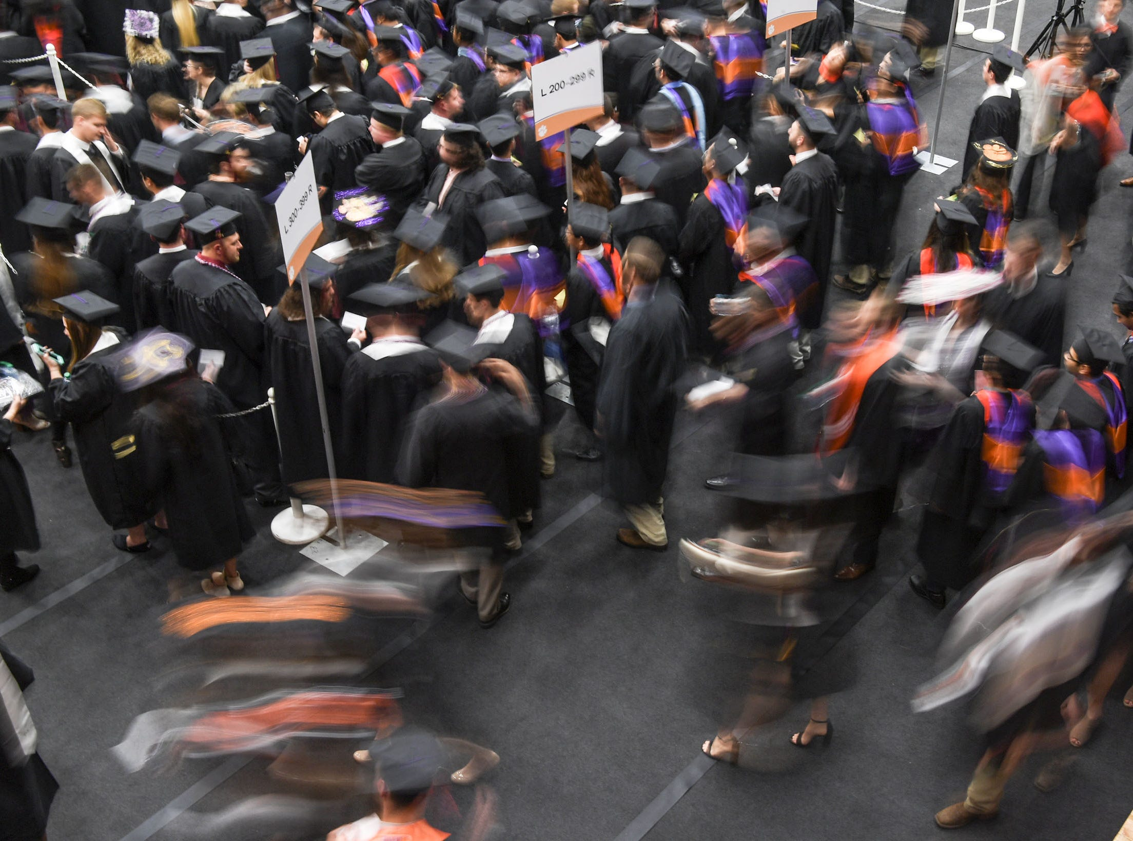 Graduates gather in a back room area before the Clemson University morning graduation ceremony Thursday morning in Littlejohn Coliseum in Clemson.