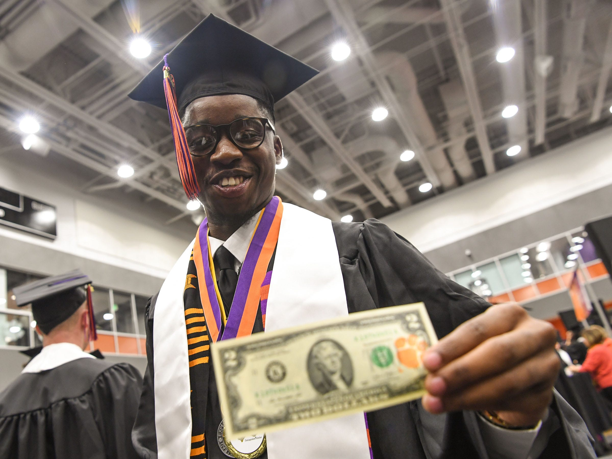 Willie Webb of Beafort, S.C. holds a Tiger Two dollar bill before the Clemson University morning graduation ceremony Thursday morning in Littlejohn Coliseum in Clemson.