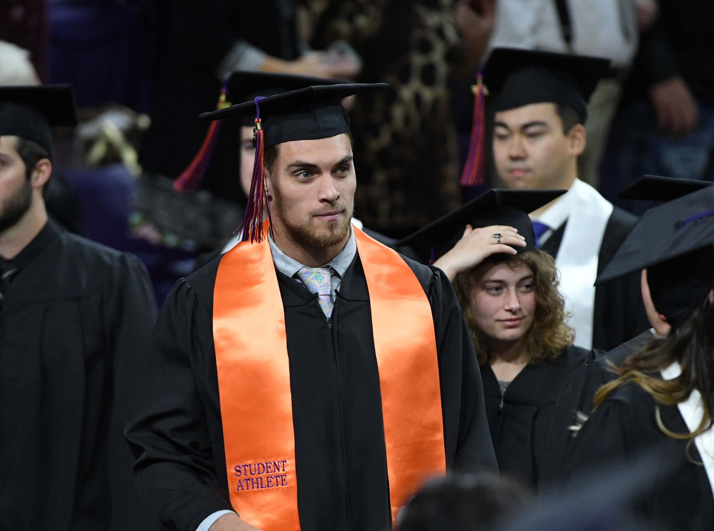 Clemson football defensive back Tanner Muse, a parks, recreation & tourism management major, walks in for the Clemson University graduation ceremony Thursday morning in Littlejohn Coliseum in Clemson.