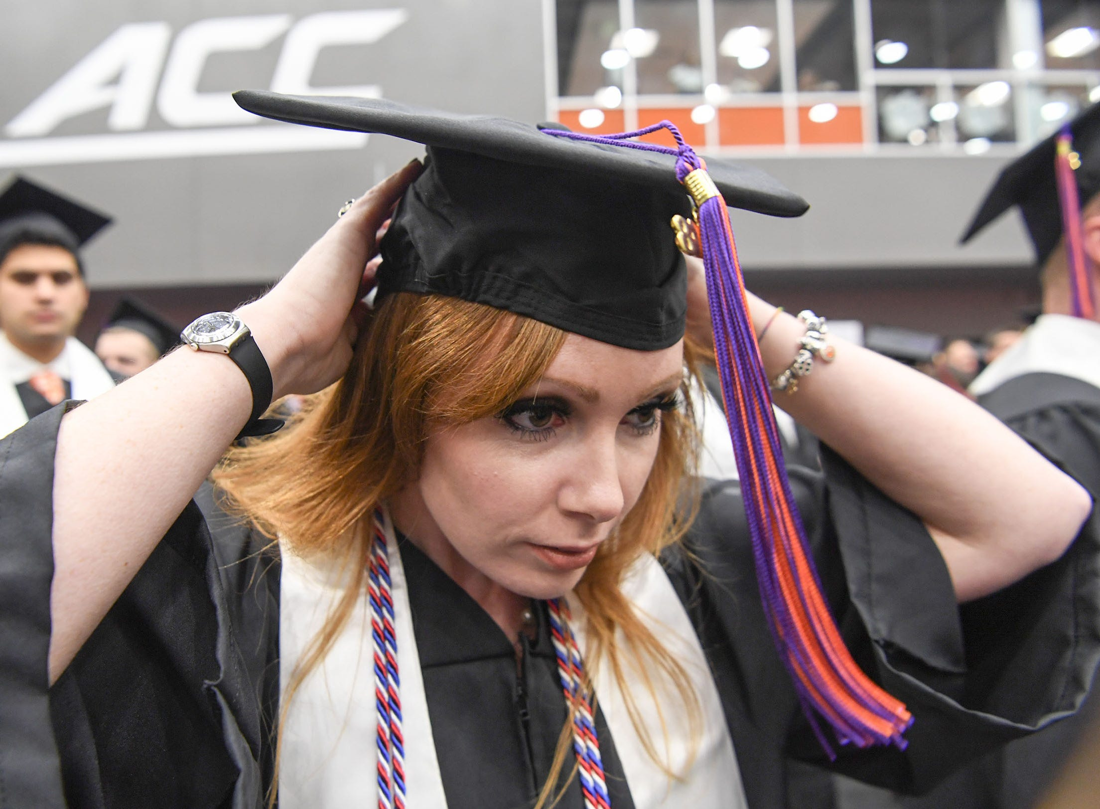 Amanda Nicks, psychology major, adjusts her cap before the Clemson University graduation ceremony Thursday morning in Littlejohn Coliseum in Clemson.