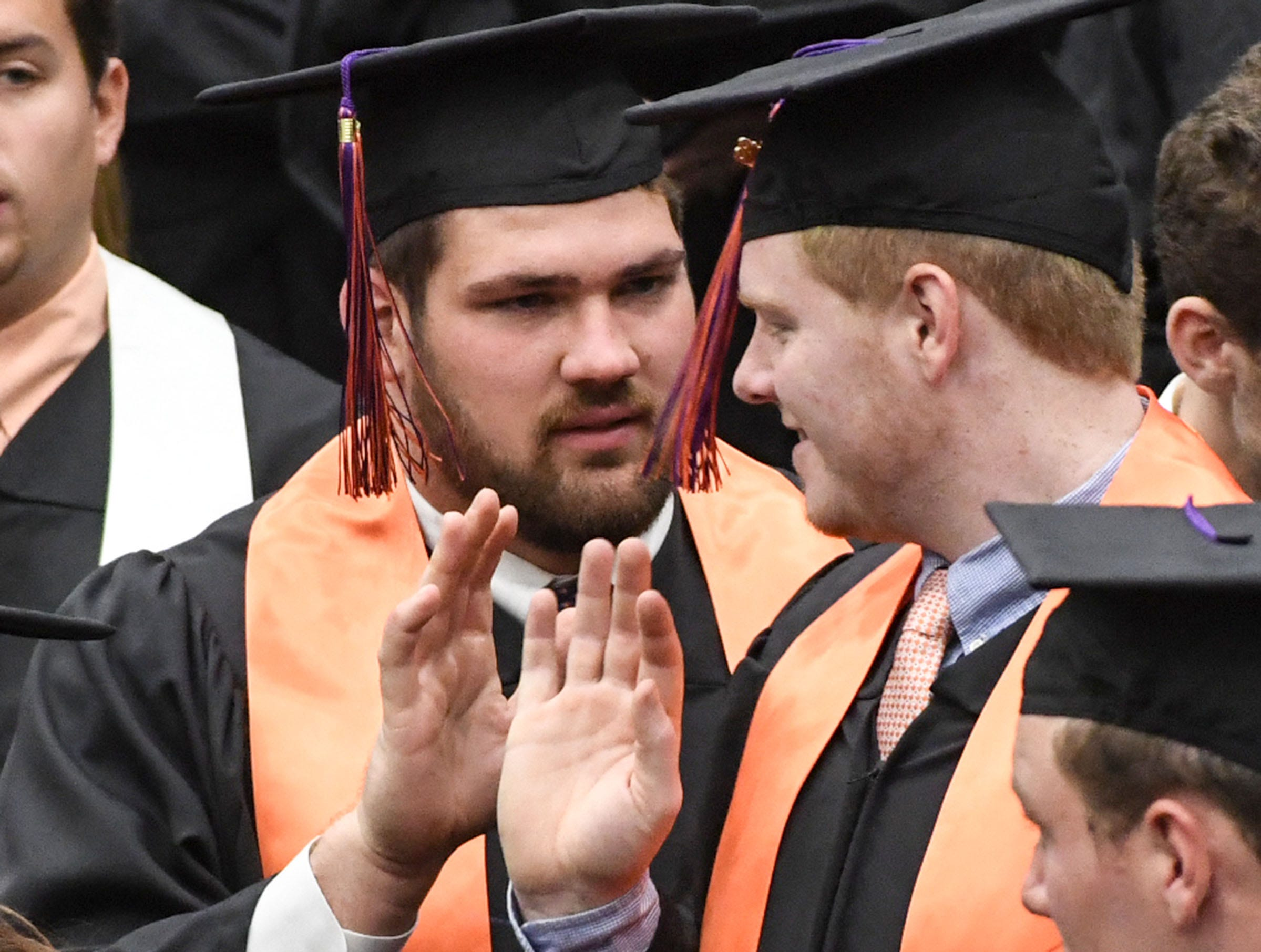 Clemson offensive lineman Gage Cervenka, left, a criminal justice major, gives a high five to football teammate and graduate Zach Giella before the Clemson University morning graduation ceremony Thursday morning in Littlejohn Coliseum in Clemson.