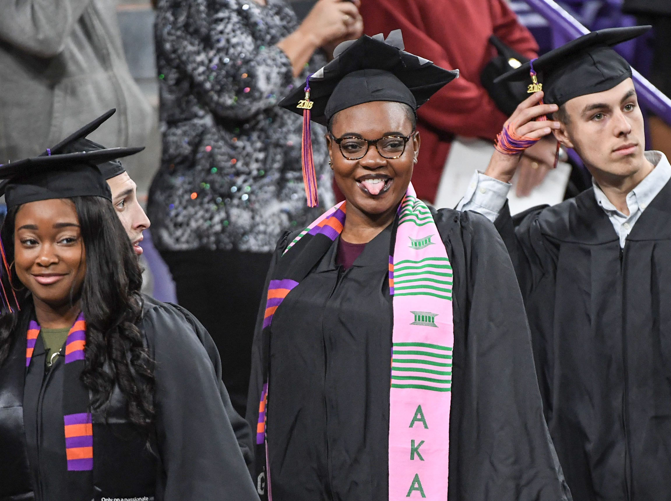 Barbara Dinkins, middle, reacts as she arrives in the arena for the Clemson University morning graduation ceremony Thursday morning in Littlejohn Coliseum in Clemson.