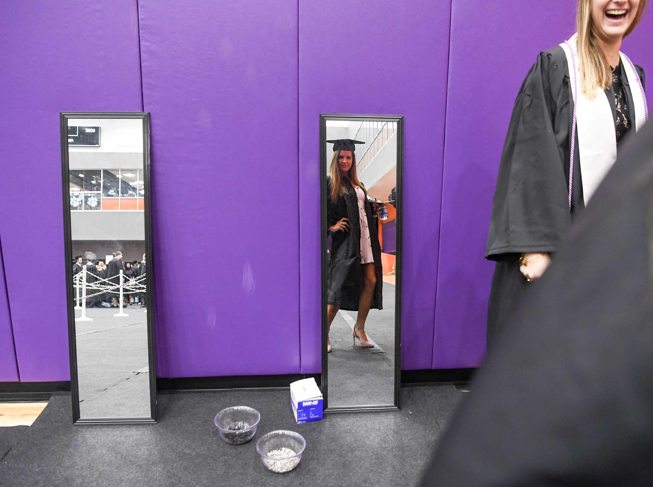 Natalie Feagin of Murrels Inlet looks in the mirror before the morning Clemson University graduation ceremony Thursday morning in Littlejohn Coliseum in Clemson.