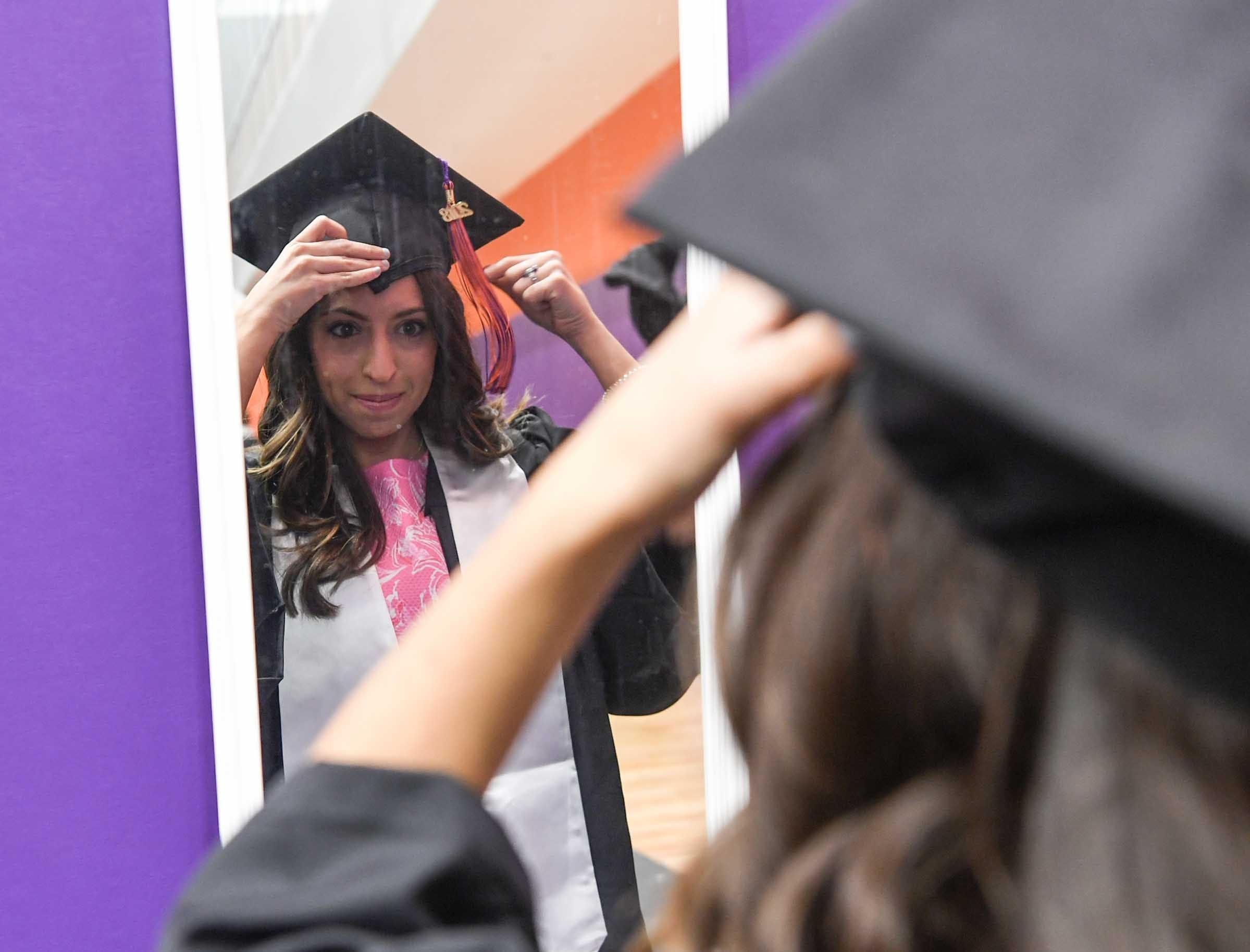 Sarah Jordan of Lancaster, S.C. fixes her cap during Clemson University graduation ceremony Thursday morning in Littlejohn Coliseum in Clemson.