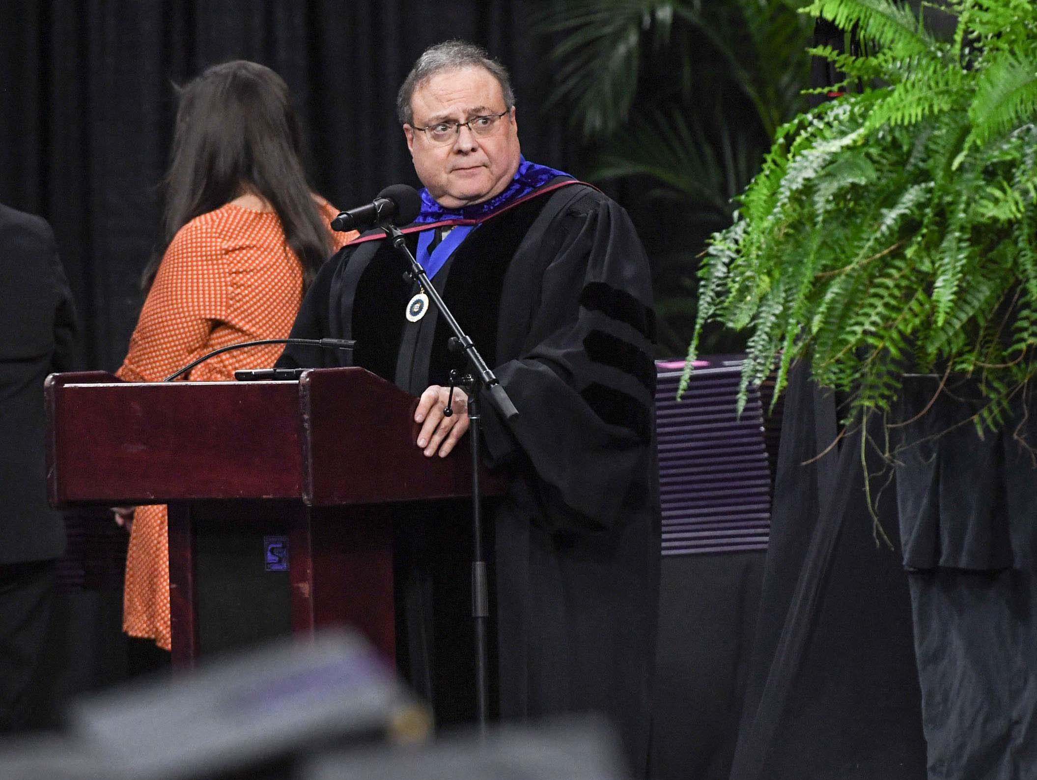 Peter Cohen reads names during Clemson University graduation ceremony Thursday morning in Littlejohn Coliseum in Clemson.