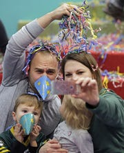 Jeff and Amanda Braunreiter of Appleton get a photo with their children Jack and Emerson following the Noodles Around the World New Year's Eve celebration at the Building for Kids Children's Museum on New Year's Eve in 2017.