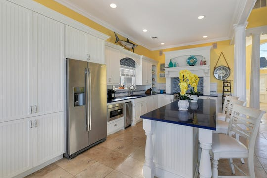 The kitchen features customized cabinets and new quartz center island and countertops.