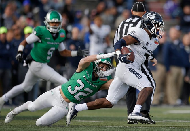 Utah State cornerback D.J. Williams (7) evades North Texas wide receiver Michael Lawrence (32) after an interception during the first half of the New Mexico Bowl in Albuquerque, N.M., Saturday, Dec. 15, 2018.