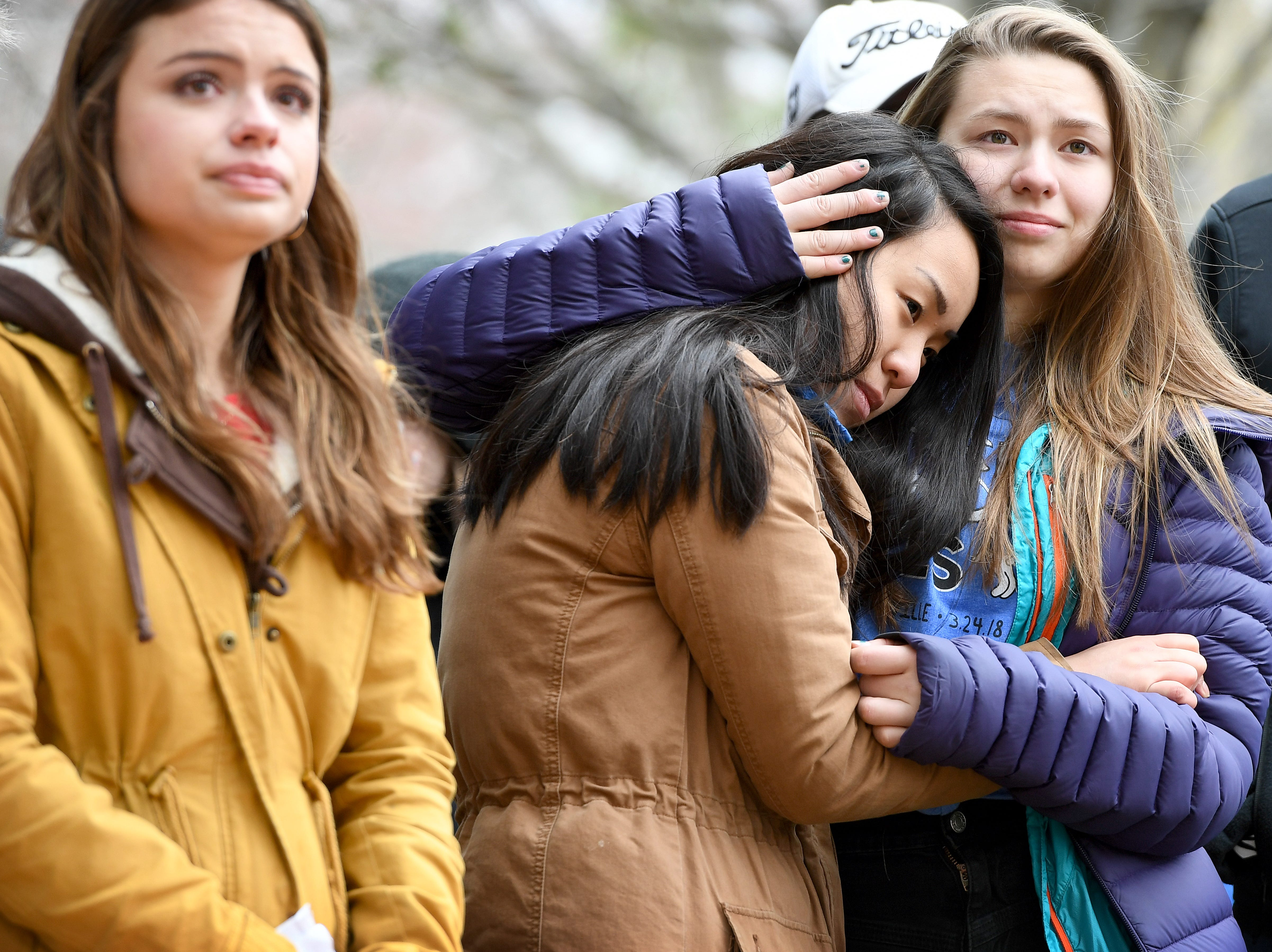 March organizers and Reynolds High School students junior Hannah Kepple, 17, left, junior Audrey Meigs, 16, center, and senior Aryelle Jacobsen, 17, listen as the names of the victims of last month's shooting at Stoneman Douglas High School in Parkland Florida are recited at Martin Luther King, Jr. Park during the Asheville March for Our Lives on Saturday, March 24, 2018.