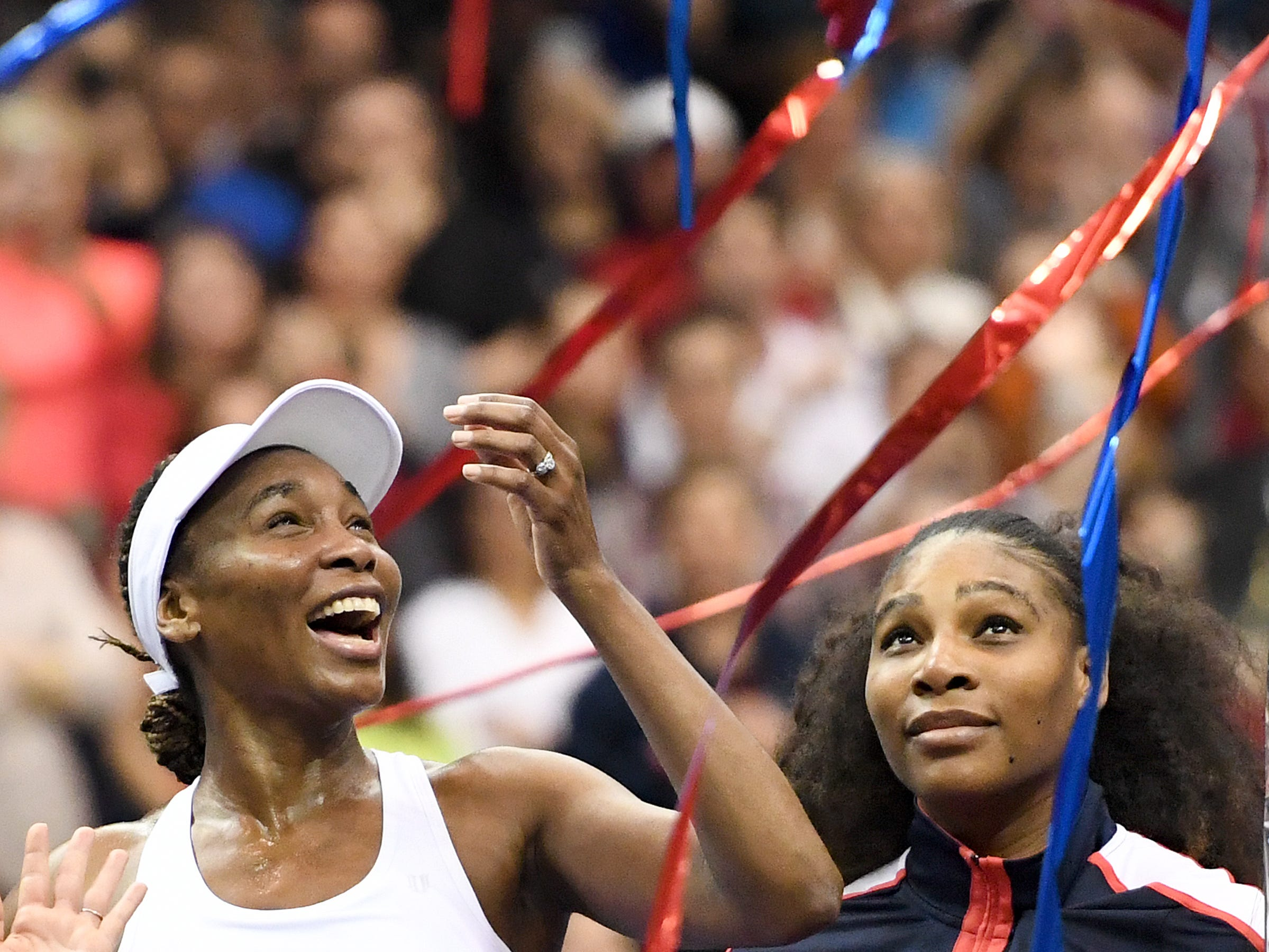 Venus Williams stands with her sister, Serena, after she defeated the Netherlands' Richel Hogenkamp clinching a win for the United States in the first round of the 2018 Fed Cup at the U.S. Cellular Center on Sunday, Feb. 11, 2018.