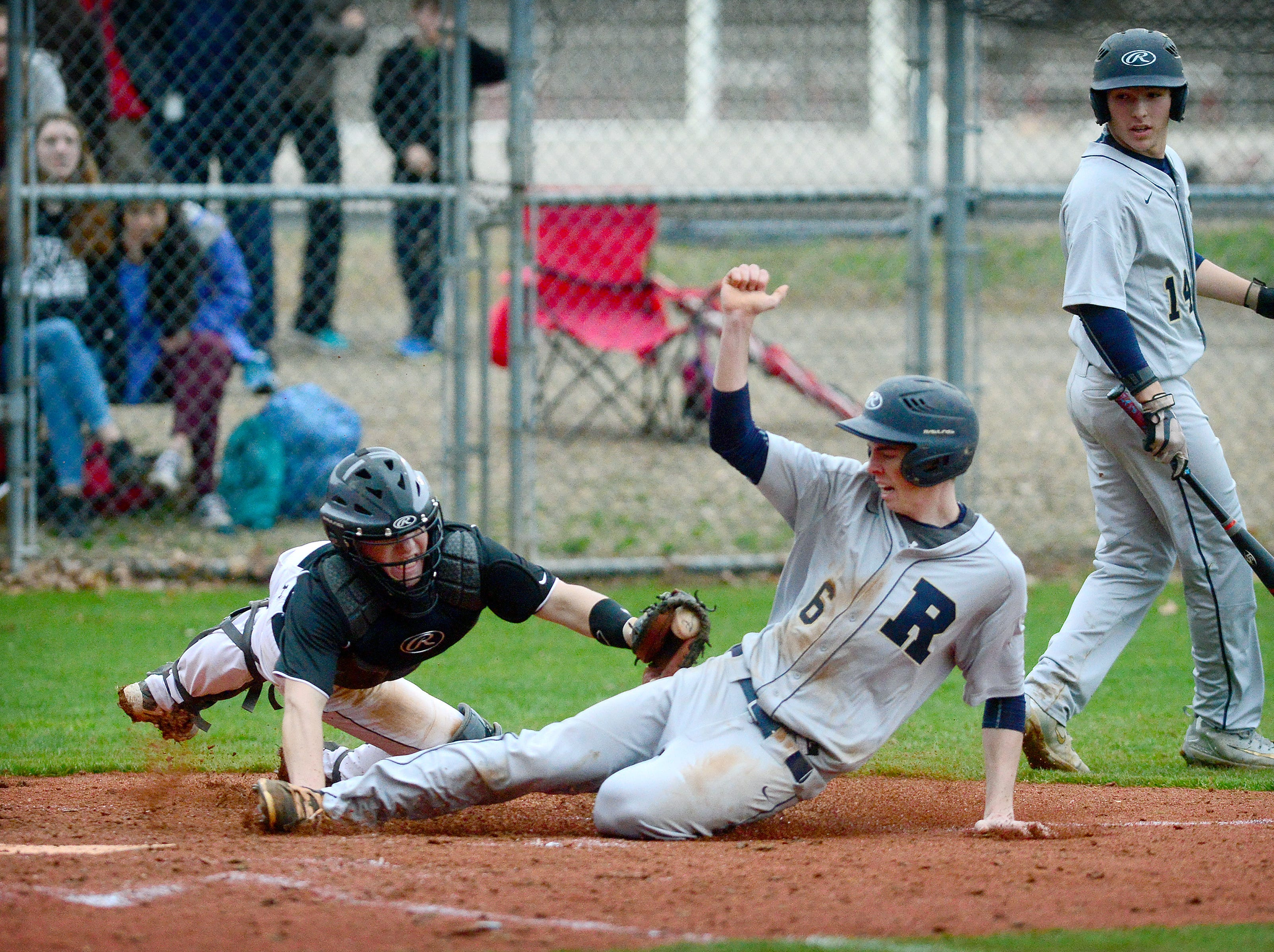 Roberson's Ethan Miller narrowly misses the tag from Asheville catcher Three Hillier as he slides safely into home plate to score a run during their game at Asheville High School on Wednesday, Feb. 28, 2018. The Cougars went on to defeat the Rams 6-5 in five innings. The game was called due to darkness.