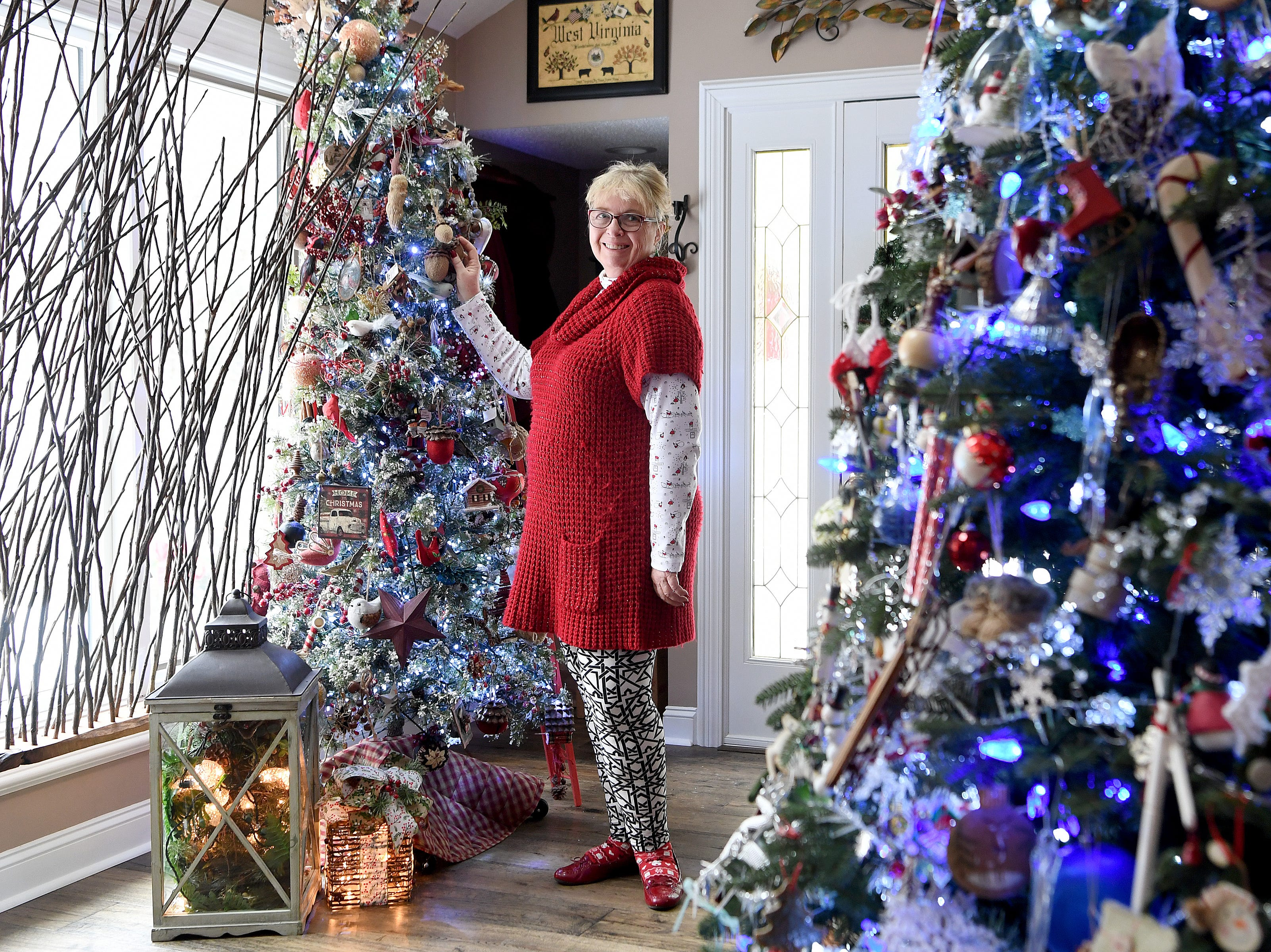 "Phyllis Bryan stands between two of the five large decorated trees she puts up each year in her Waynesville home. ""It's a way to think about how blessed you are and how you've been blessed and touched by so many other people,"" she said about decorating for Christmas and pulling out the many things she has collected over the years."