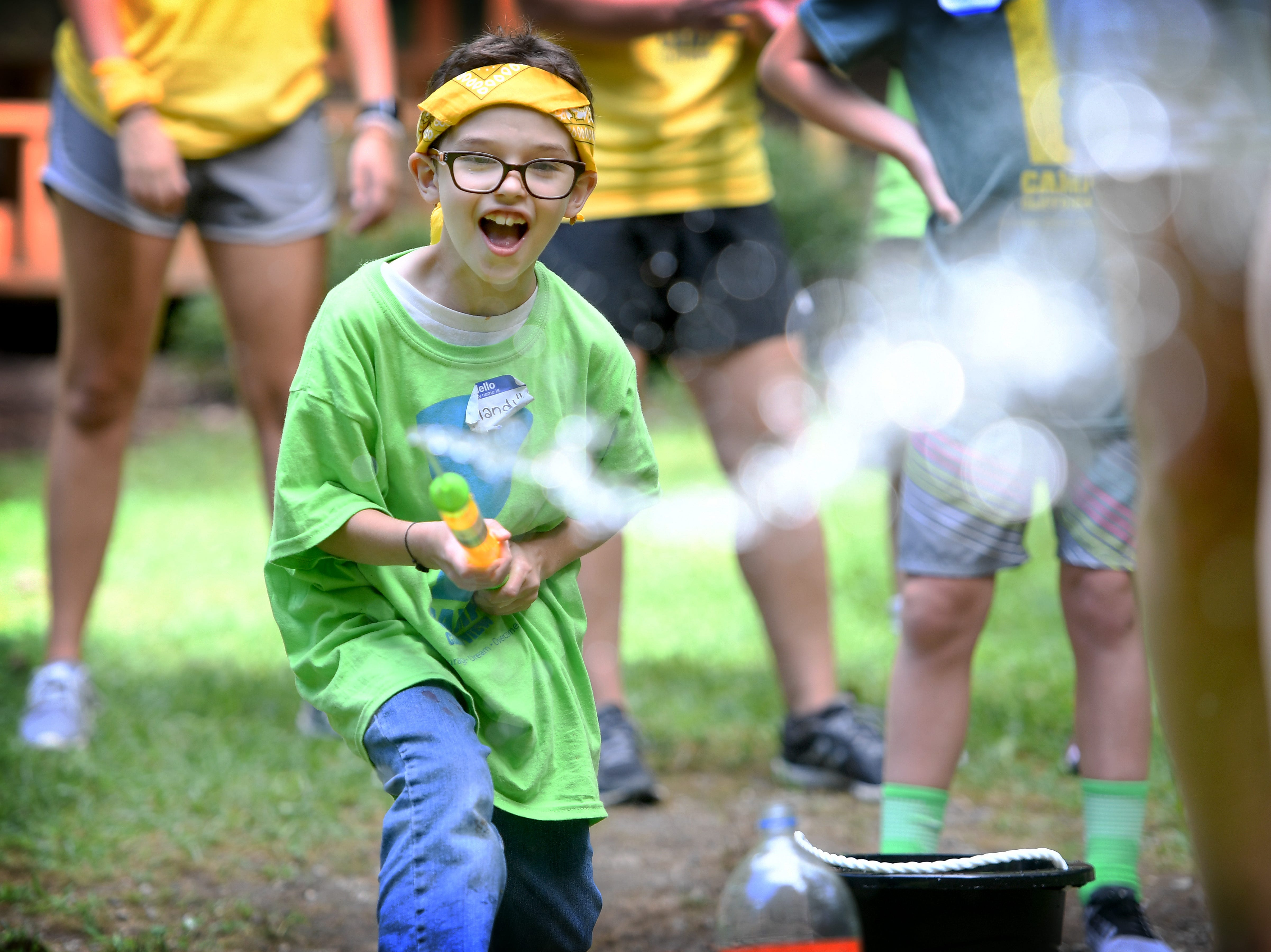 Ryland Rice, 8, shoots a squirt cannon at a ball as he runs a team-building relay race during Camp Cliffview at Camp Ton-A-Wanda in Hendersonville on Saturday, Aug. 11, 2018. The camp is a one-day outdoor experience for students with special needs. This year's camp served 16 campers from Henderson, Transylvania and Buncombe Counties utilizing more than 50 volunteers and 20 counselors. The camp, which originated in Tennessee, was held in Hendersonville for the second year and was fully funded thanks to community sponsors.
