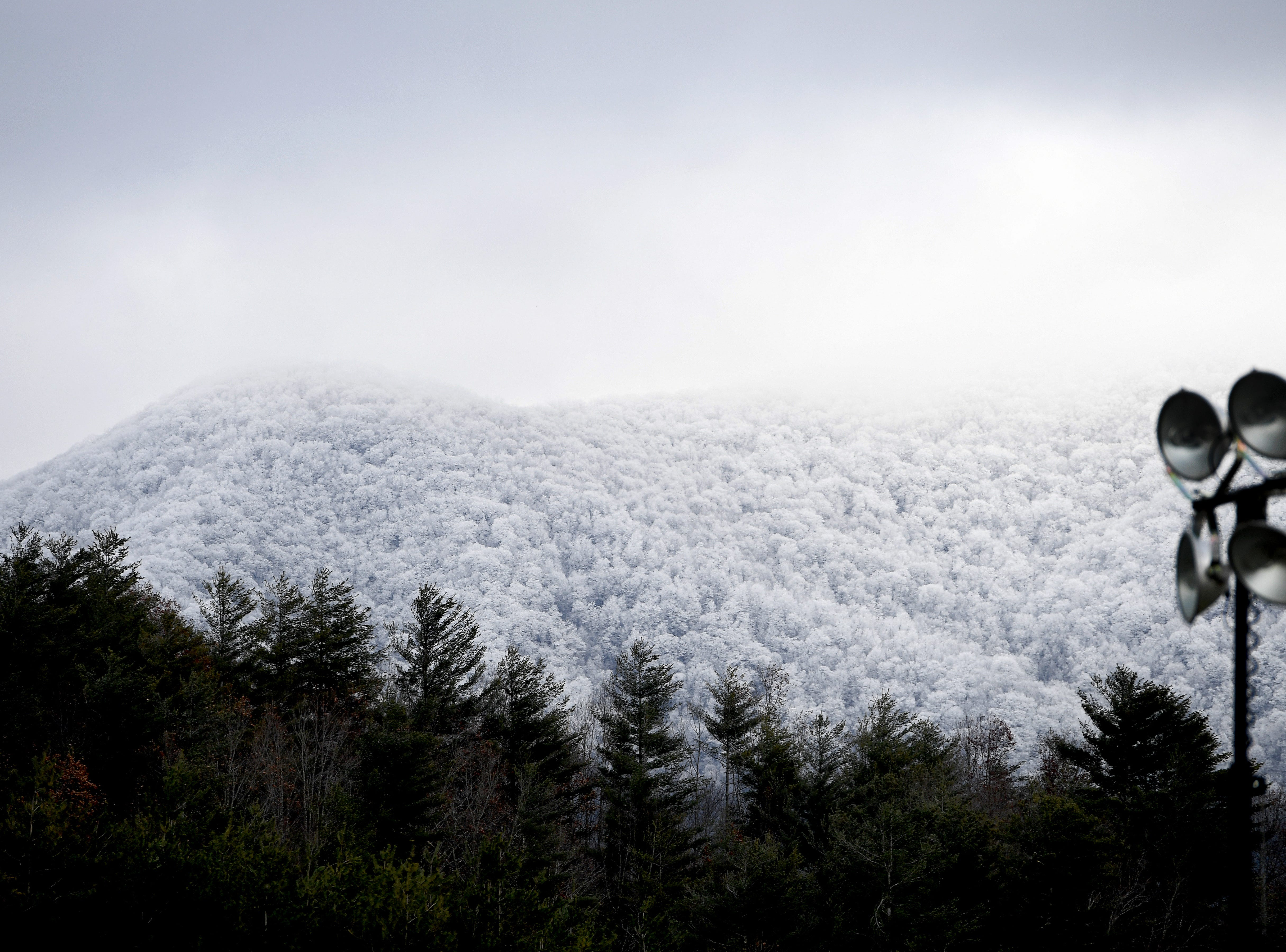 As snow flurries lightly fall on Mitchell High School Mountaineer football practice a nearby mountaintop is blanketed in white on Nov. 27, 2018.