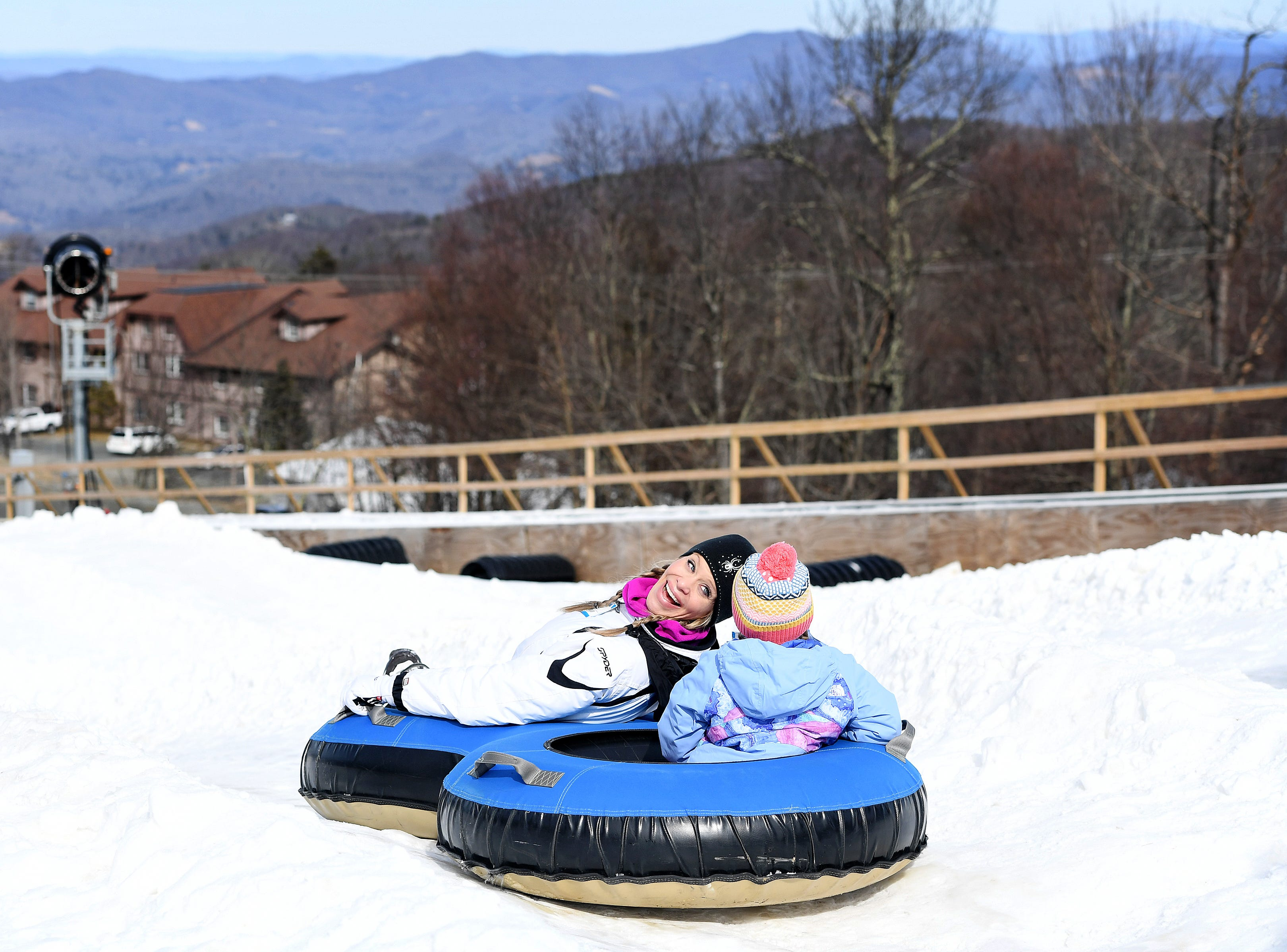 Courtney Hilliard looks back at her daughter, Madeline, 5, of Cherryville, North Carolina, as they prepare to make their way down a tubing run at  Beech Mountain Resort in Beech Mountain on Friday, Jan. 26, 2018. The resort is celebrating its 50th birthday this year.