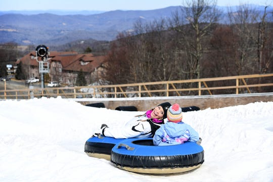 Courtney Hilliard looks back at her daughter, Madeline, 5, of Cherryville, North Carolina, as they prepare to make their way down a tubing run at Beech Mountain Resort in Beech Mountain last year. The resort is open for skiing but the tubing run will open in early December.