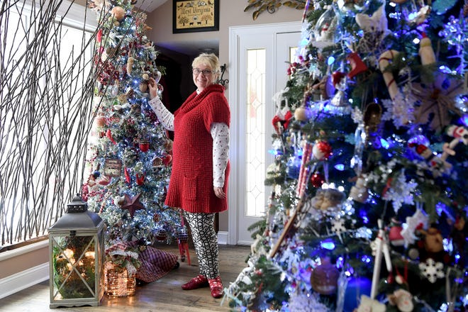 """Phyllis Bryan stands between two of the five large decorated trees she puts up each year in her Waynesville home. """"It's a way to think about how blessed you are and how you've been blessed and touched by so many other people,"""" she said about decorating for Christmas and pulling out the many things she has collected over the years."""