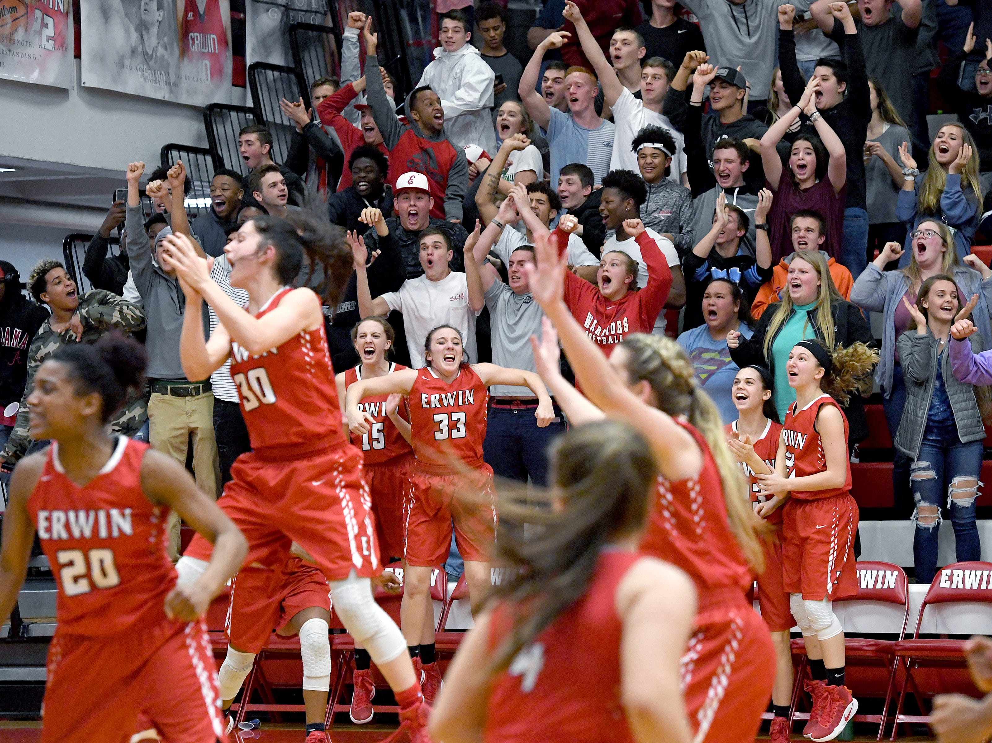 Erwin players and fans celebrate a buzzer-beater that gave the Warriors a 45-43 win over Tuscola in the championship game of the WMAC tournament at Erwin High School on Friday, Feb. 16, 2018.