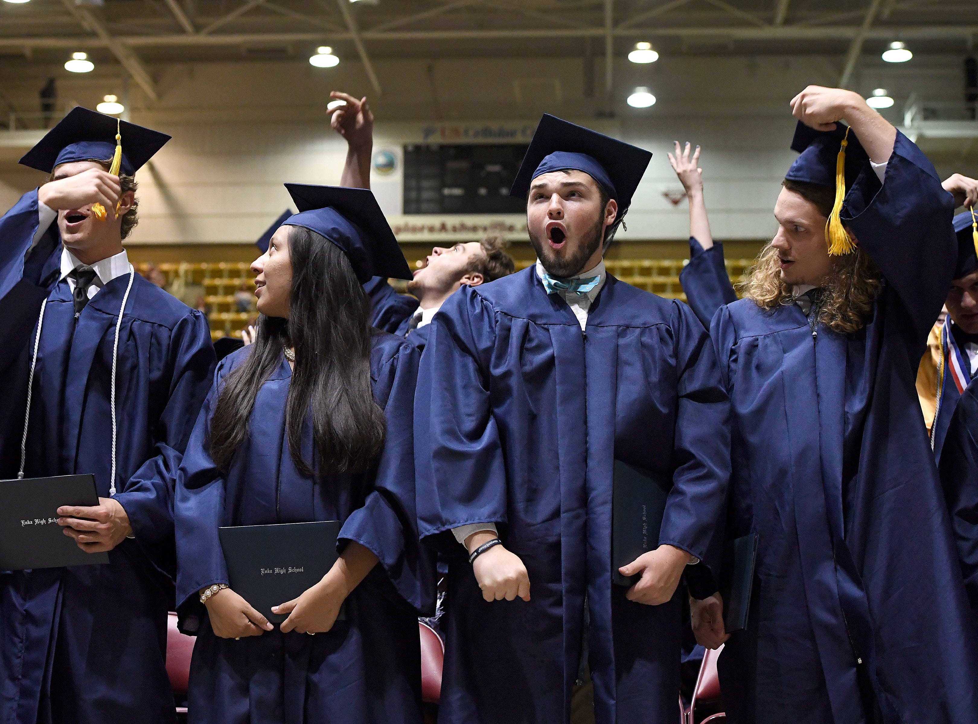 Graduates Janson Anderson, Valeria Arriaga, Christian Artus and Kevin Austin, move their tassels as their diplomas as conferred during the Enka High School Class of 2018 commencement ceremony at the U.S. Cellular Center on Friday, June 15, 2018.