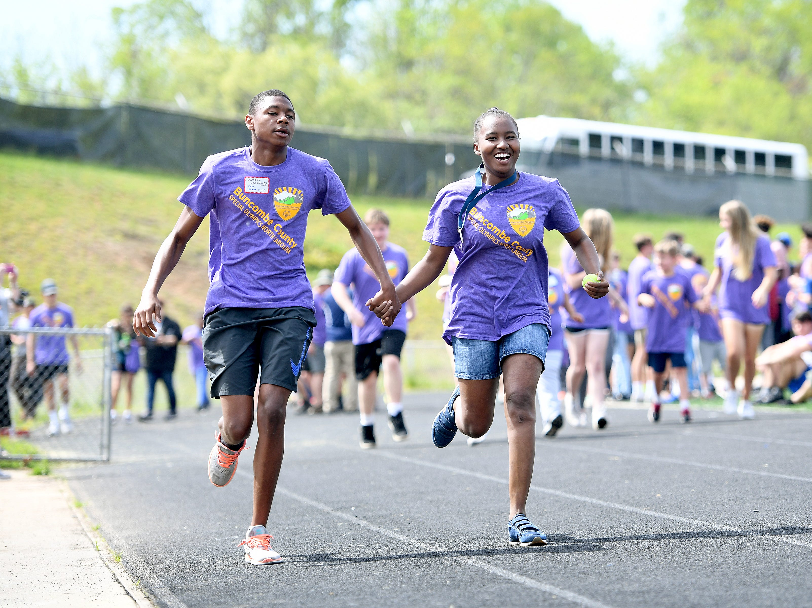 Virgil Hardaway helps his buddy, Progressive Education Program student Quatika Edgerton down the track as she competes in the 50-meter run during the Buncombe County Special Olympics Spring Games at Roberson High School on Thursday, May 3, 2018.