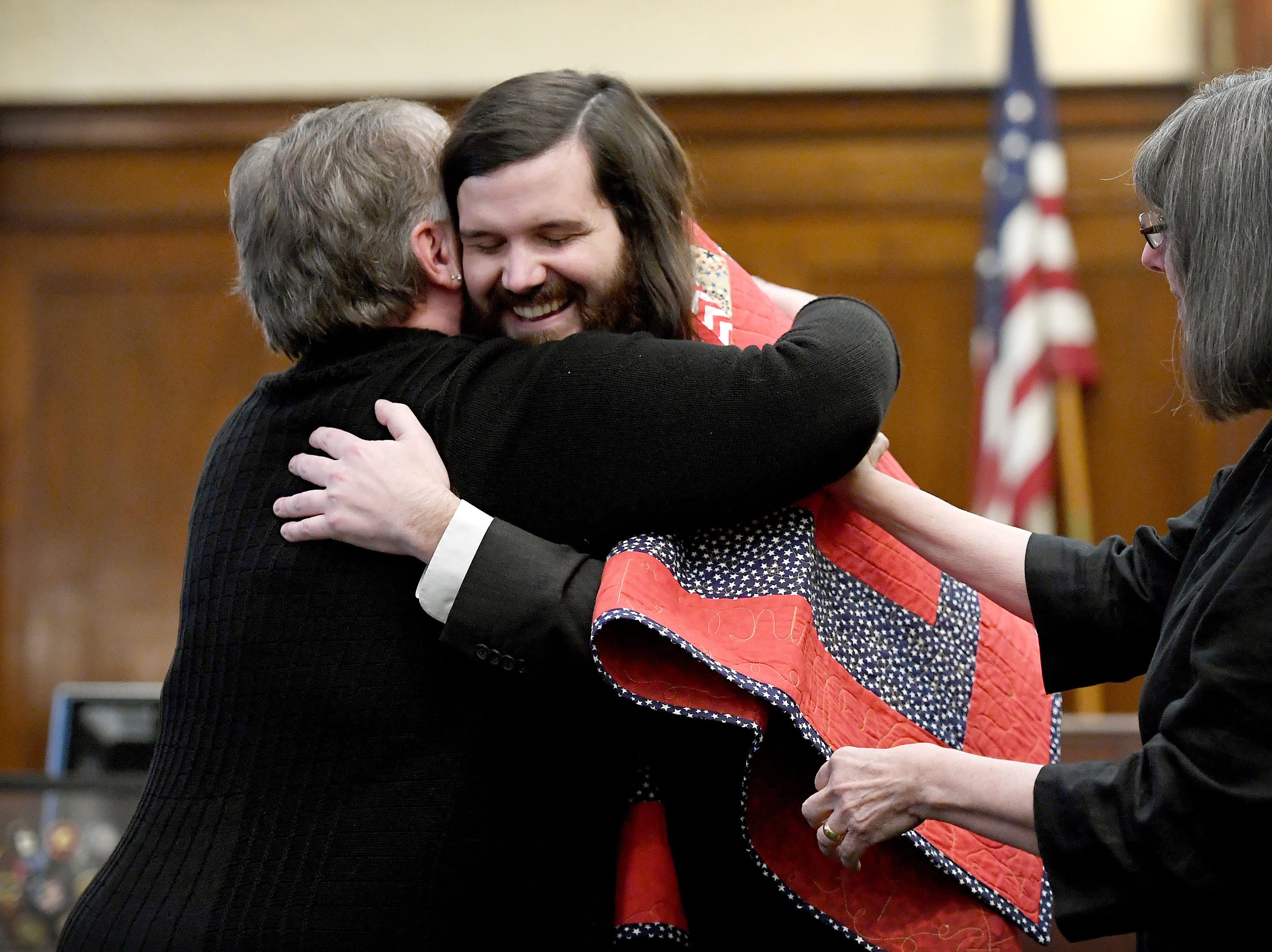 Kevin Rumley is presented with a quilt from the Welcome Home Sewing Group of the Quilts of Valor Foundation by Kerry Bonnville, left, and Melanie Greenway during the Buncombe County Veterans Treatment Court graduation ceremony on Friday, Jan. 19, 2018.