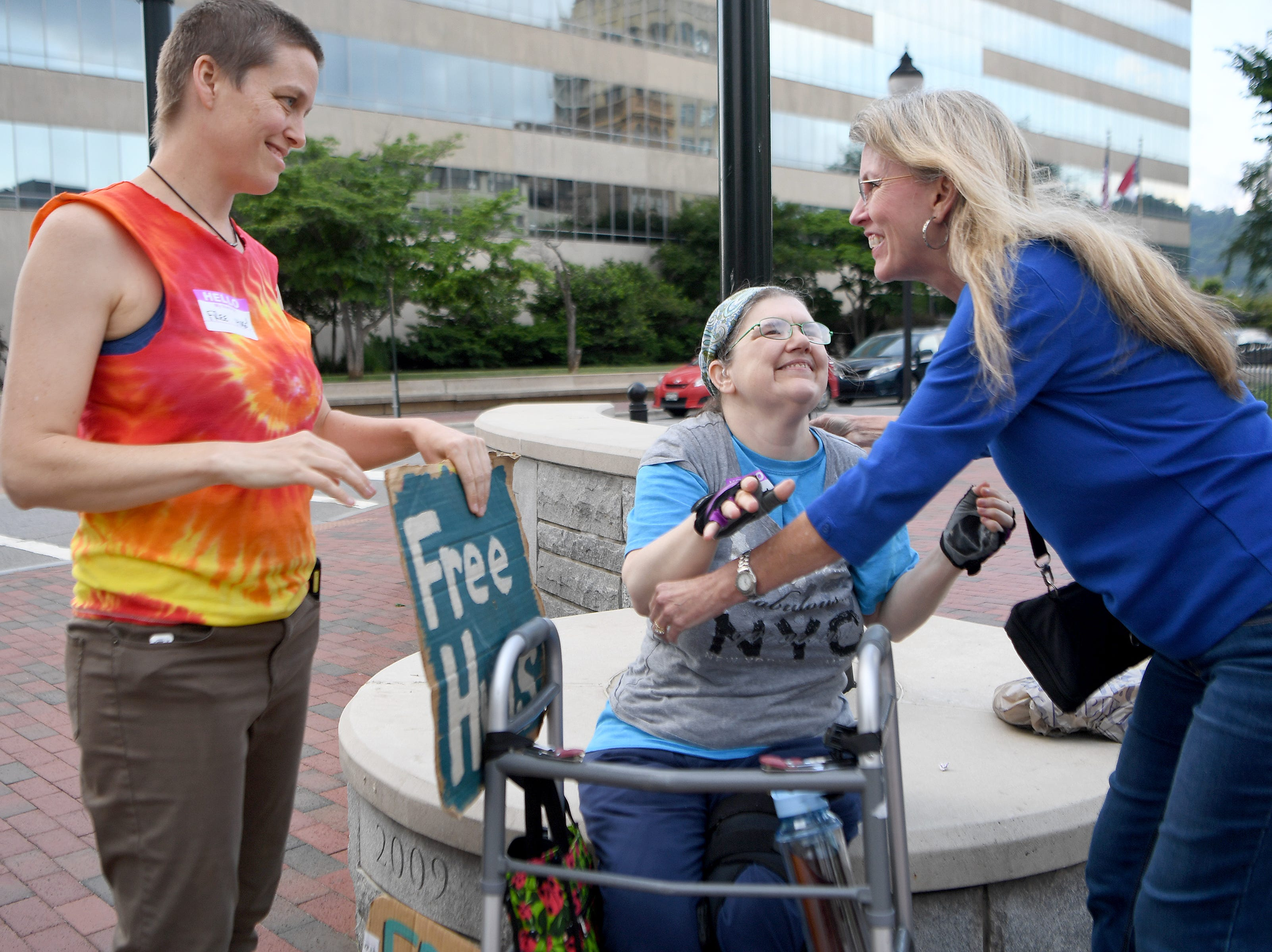 As Lena Lane looks on, Christine DeWalt gets a hug from Millie Whitney, of Augusta, during a Free Hug Flash Mob downtown on Thursday, May 24, 2018.