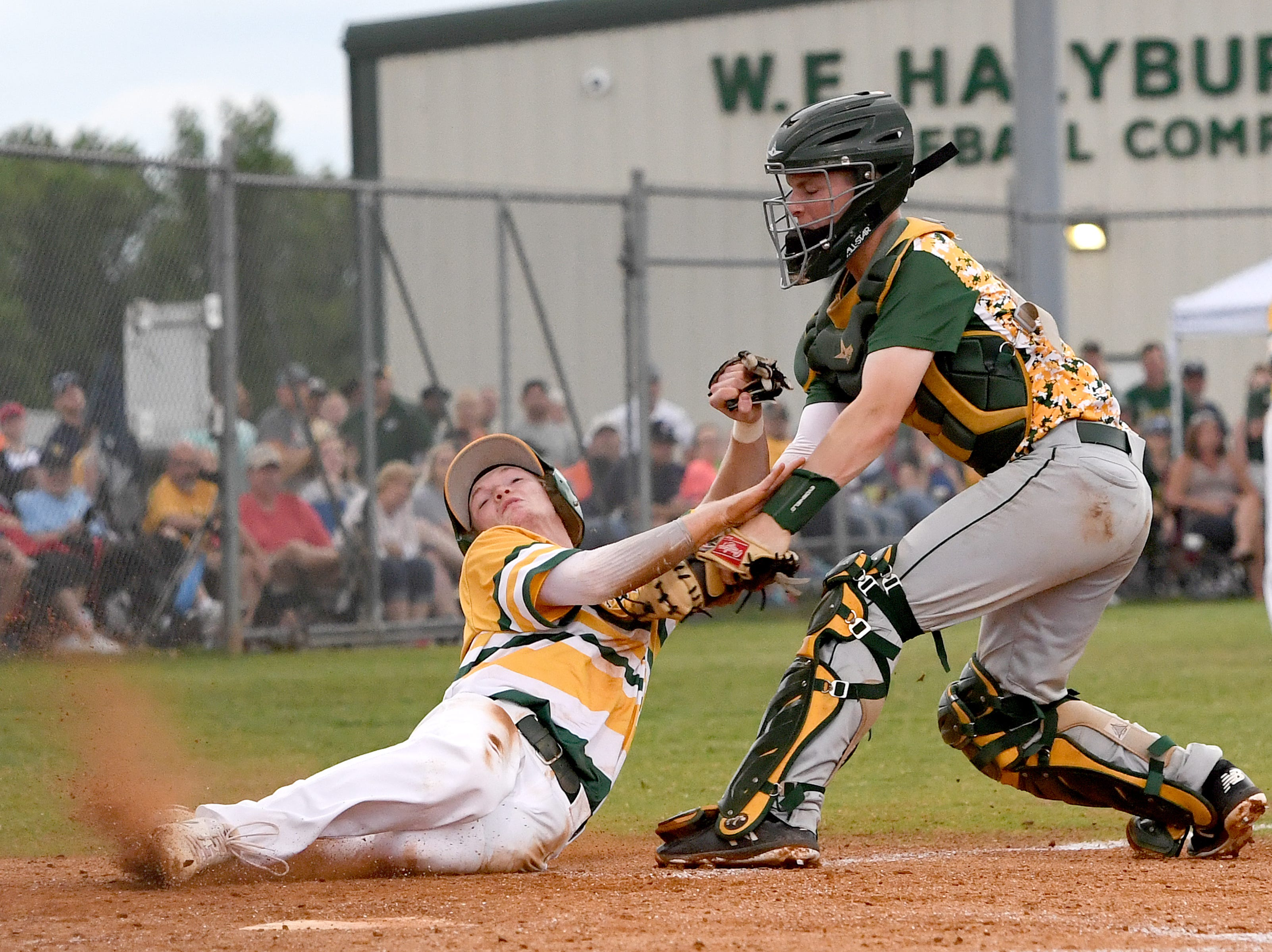 Reynolds catcher Cooper Ingle tags out Crest's Jack Millen as he slides into home plate in the third game of the NCHSAA Western Regional Championship series at Crest High School in Shelby on Saturday, May 26, 2018.