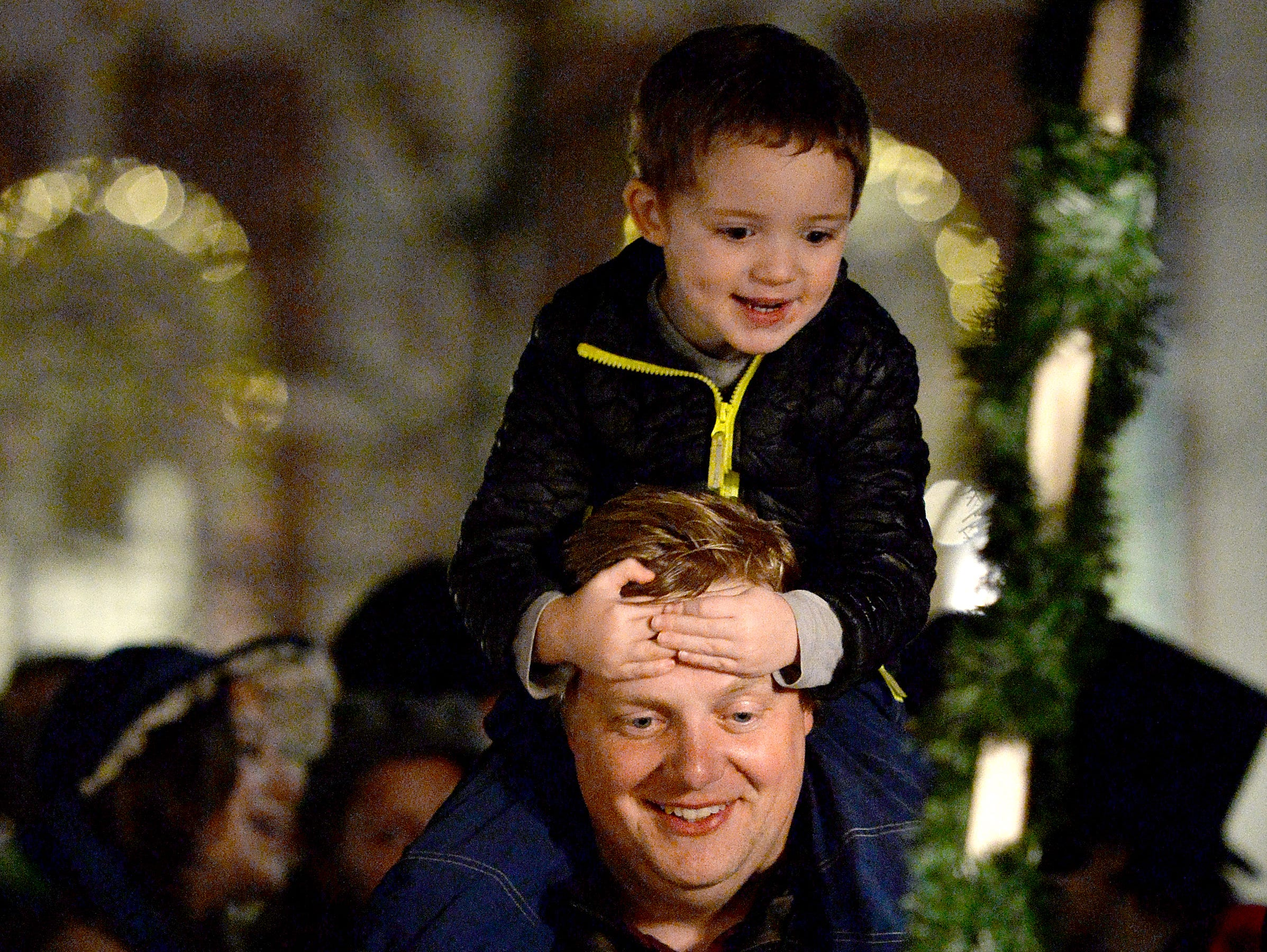 Drake Fowler, chief business and operations officer at the North Carolina Arboretum, sings along to carols with his children Jack, 3, and Adelaide, 5, during the annual Biltmore Village Dickens Festival on Nov. 30, 2018. The arboretum helped this year with the lighting design in Biltmore Village.