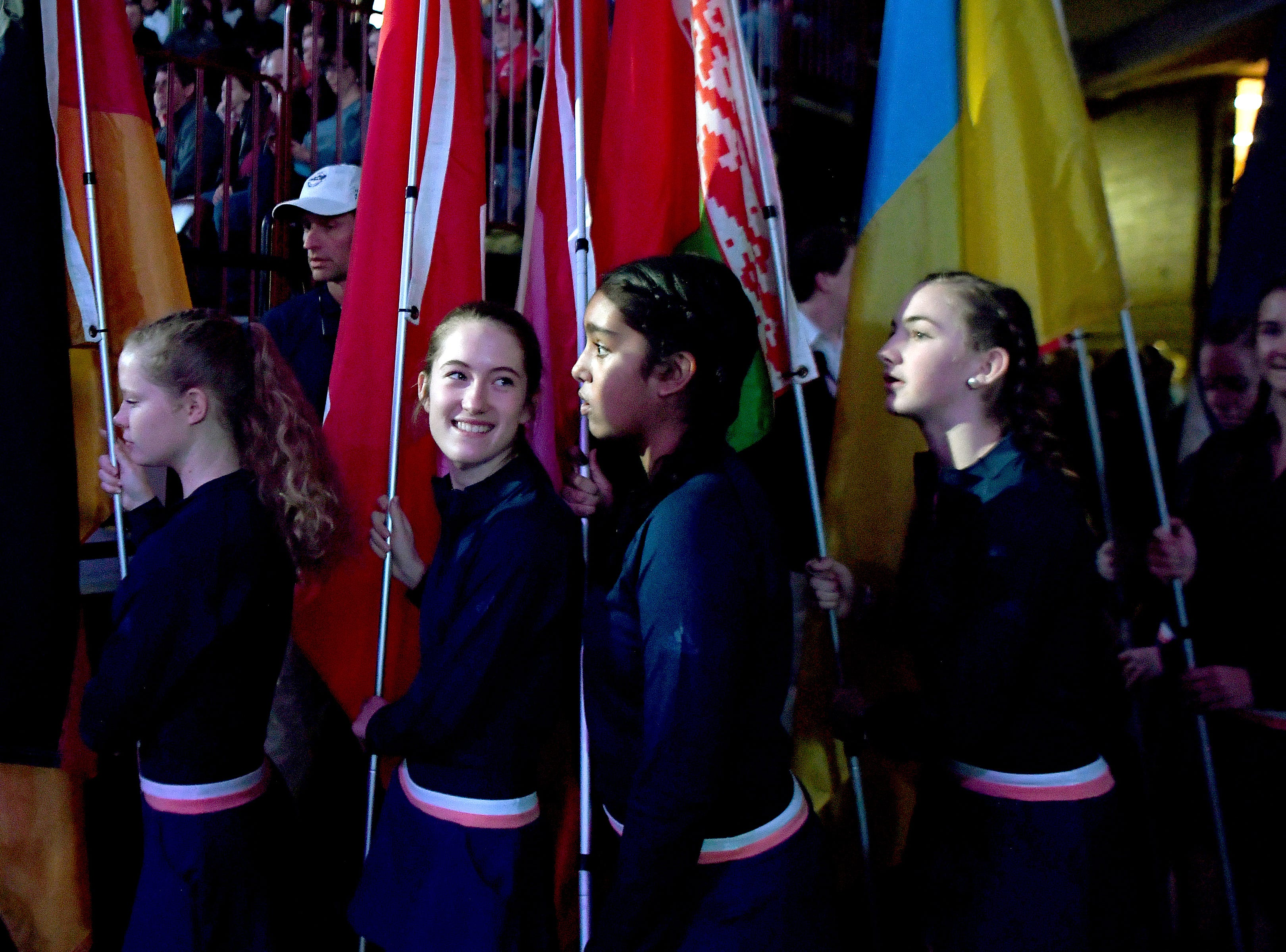 Dominique Grant looks back at Kirina Shah as they line up to take the court holding flags for the opening ceremony of the 2018 Fed Cup at the U.S. Cellular Center on Saturday, Feb. 10, 2018.