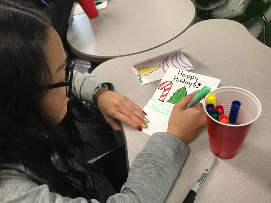 Inside Shelly Van Atta's sixth grade class at East Middle School, Jariah Durgala's classmate, Melodie, makes a card to be sent to him for Christmas.