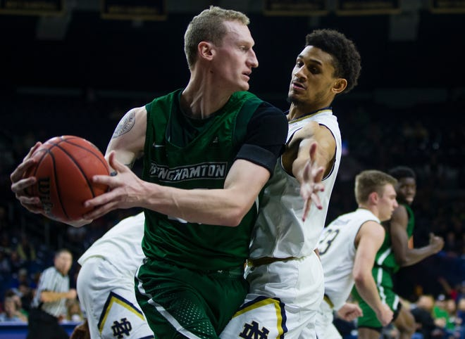 Binghamton's Caleb Stewart (20) keeps the ball away from Notre Dame's Prentiss Hubb (3) during an NCAA college basketball game Tuesday, Dec. 18, 2018 in South Bend, Ind. (Michael Caterina/South Bend Tribune via AP)