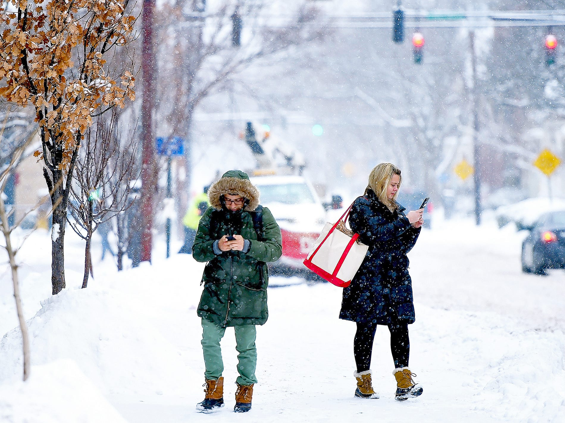 Pedestrians walk through snowy Ithaca Commons on February 7, 2018.