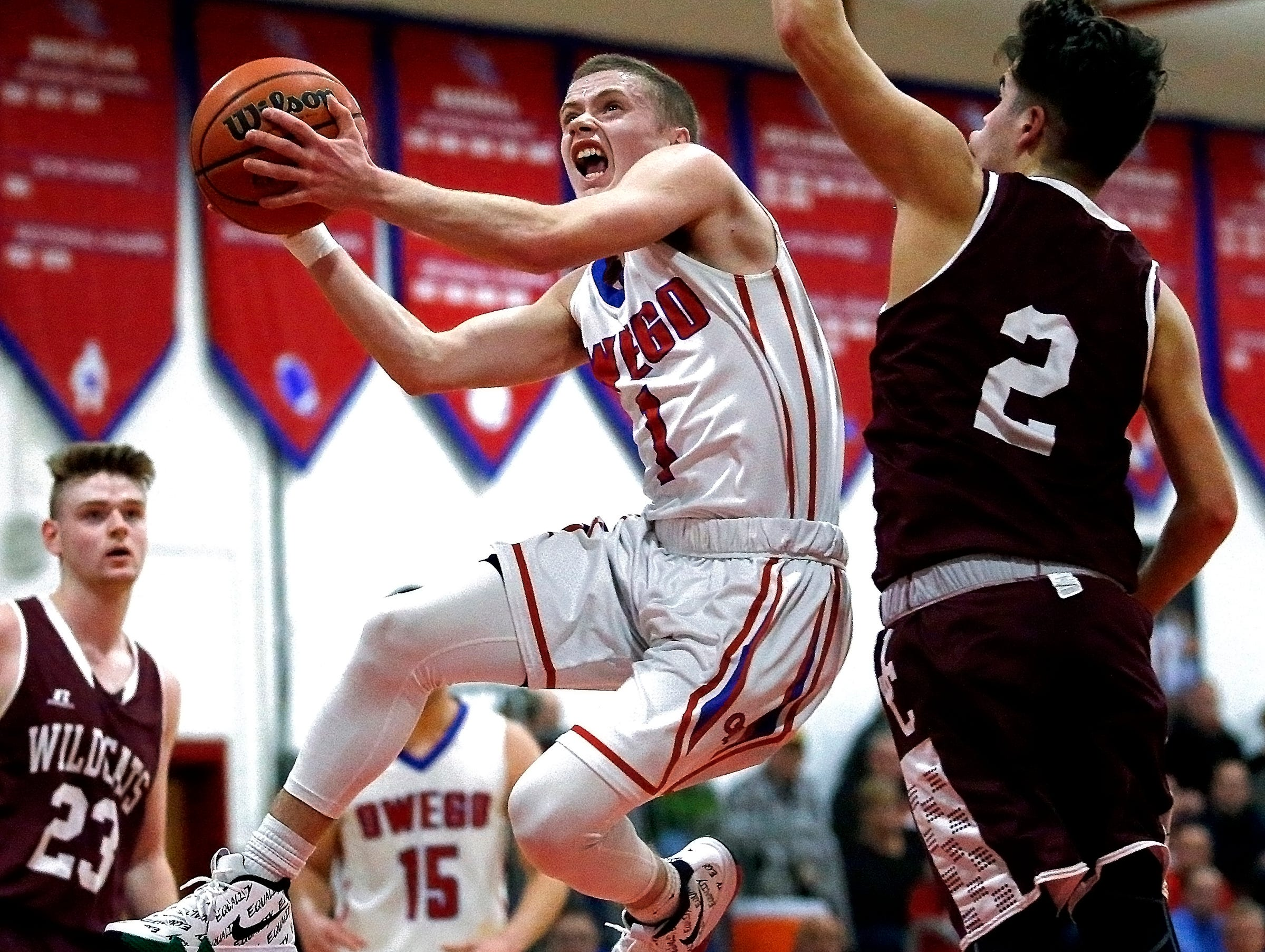Owego's Christian Sage (1) goes up to score past Johnson City's Alec Lopez (2) during Owego vs. Johnson City, Friday, January 26, 2018. Owego won in double overtime, with a final score of 76-75.
